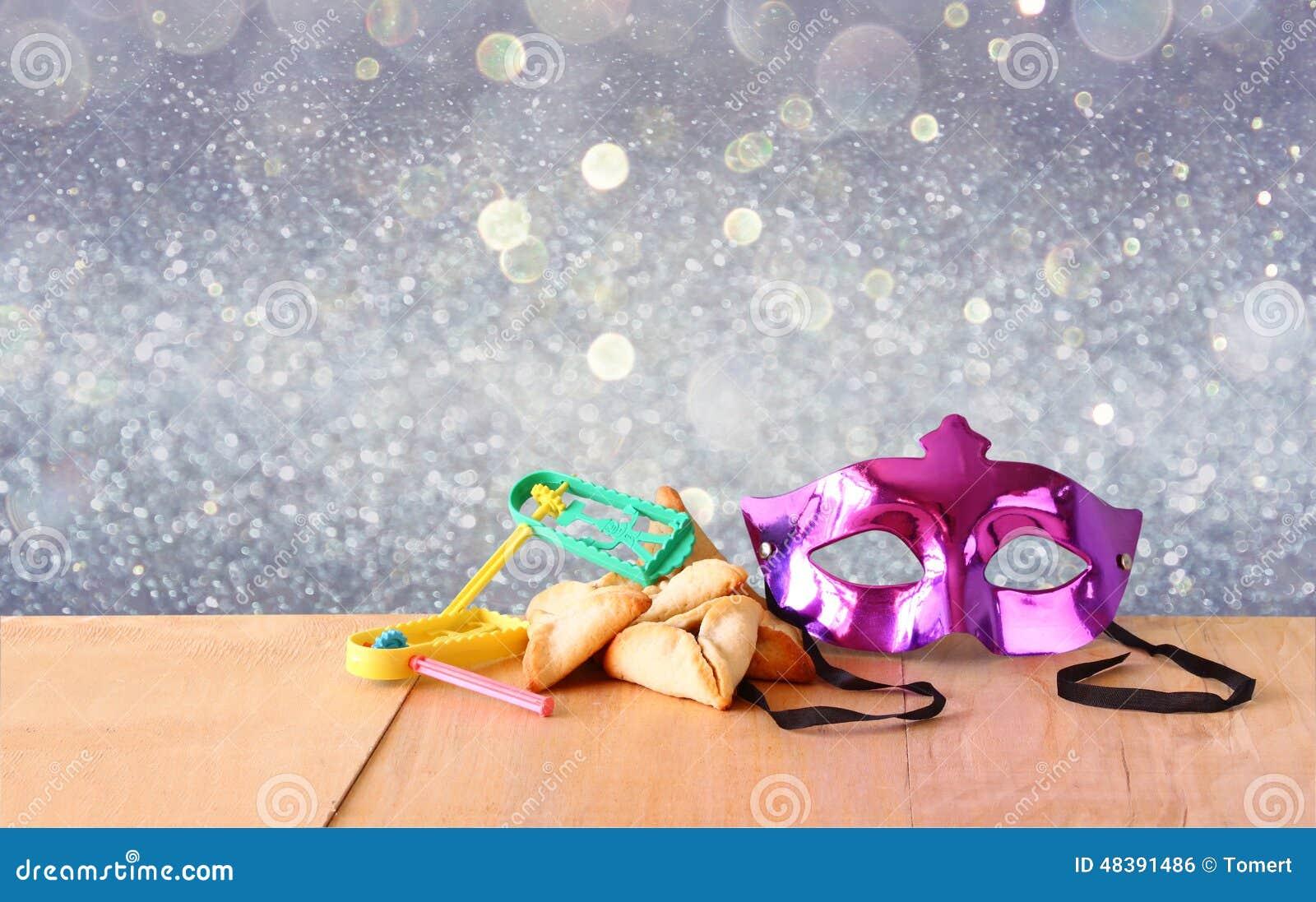 Cookies de Hamantaschen ou orelhas dos hamans, noisemaker e máscara para a celebração de Purim (feriado judaico) e fundo do brilh