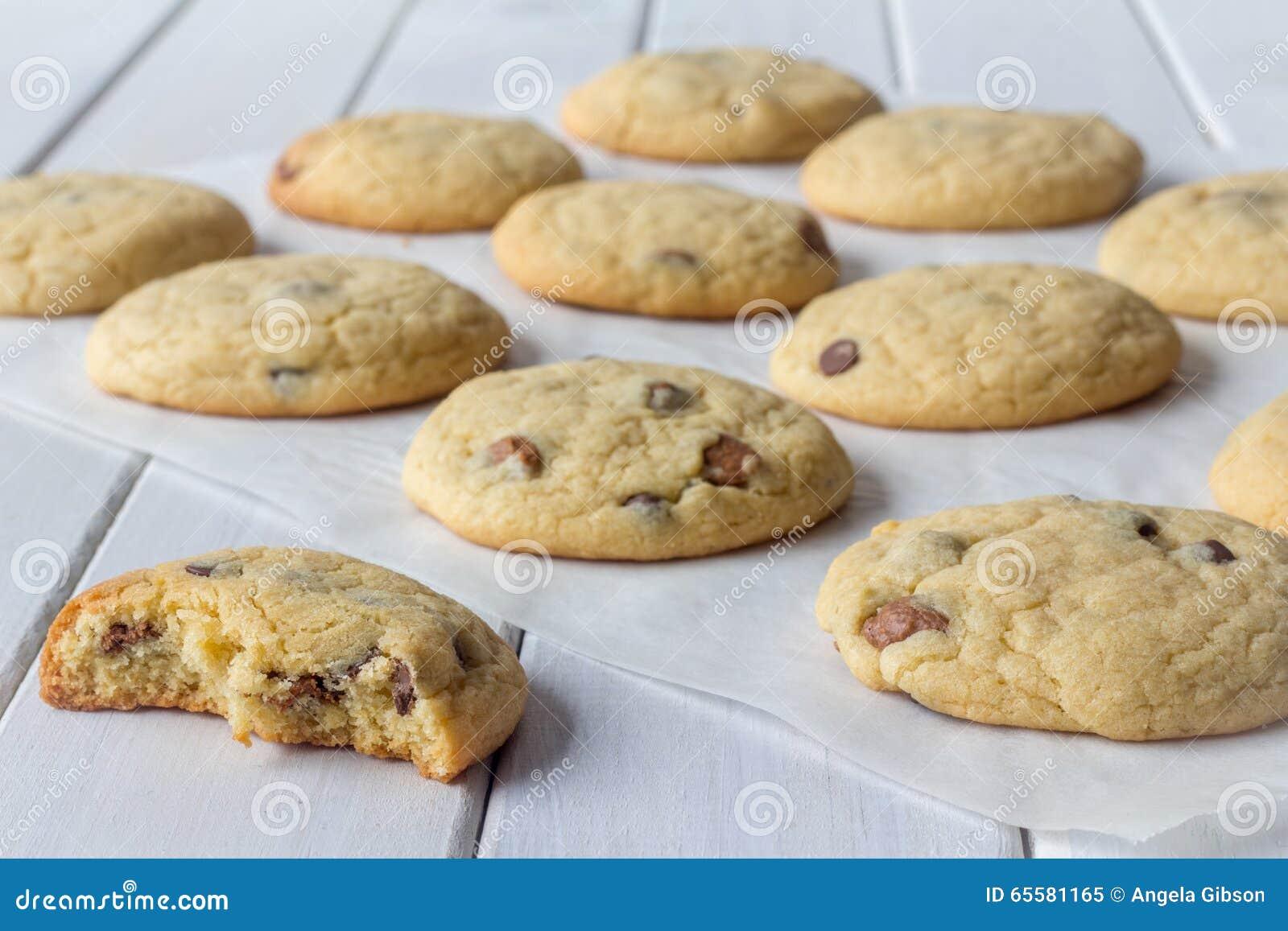 Cookies no papel do cozimento com um comido em parte