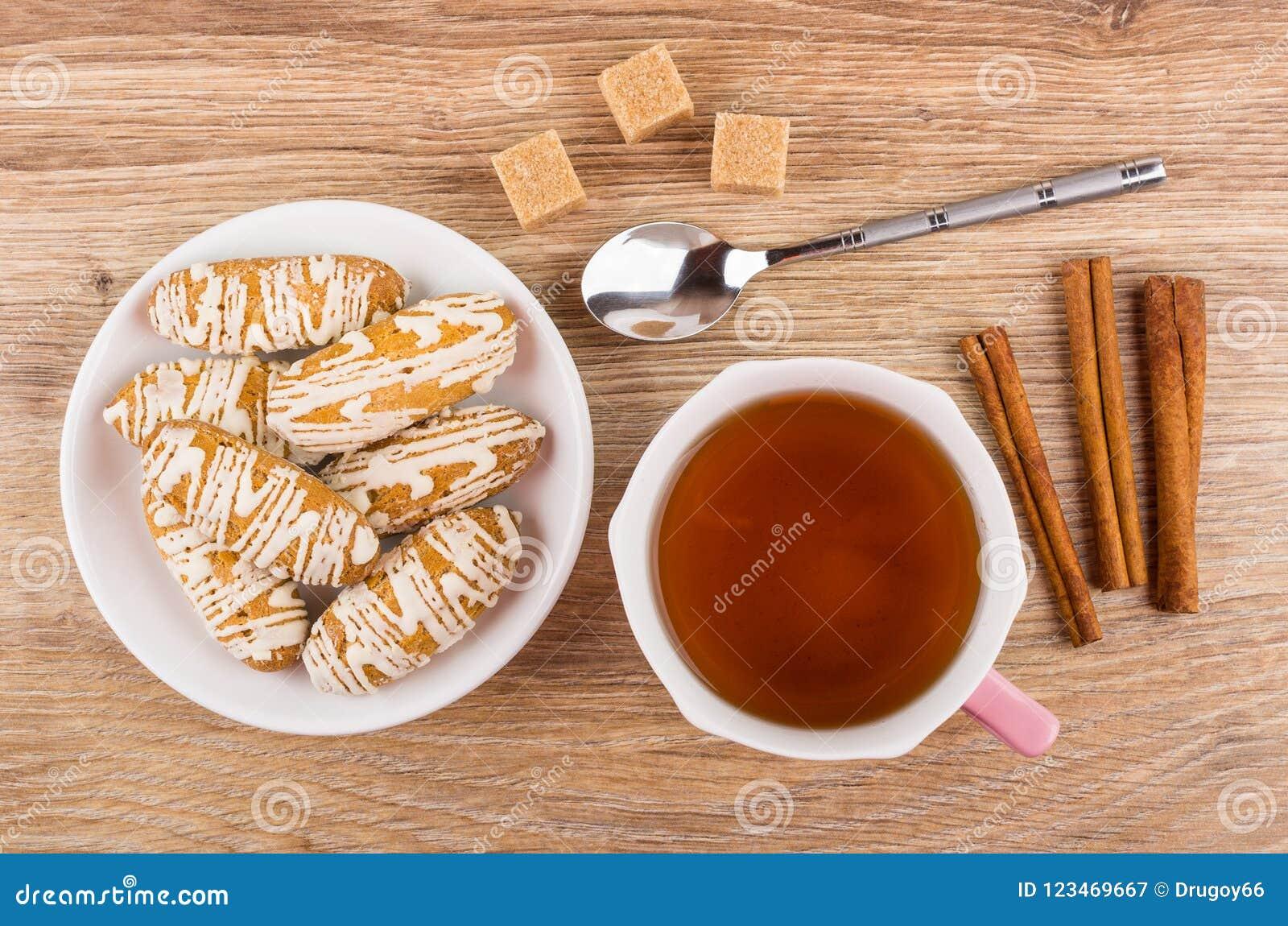 Cookies vitrificadas em uns pires, açúcar, varas de canela, colher, chá