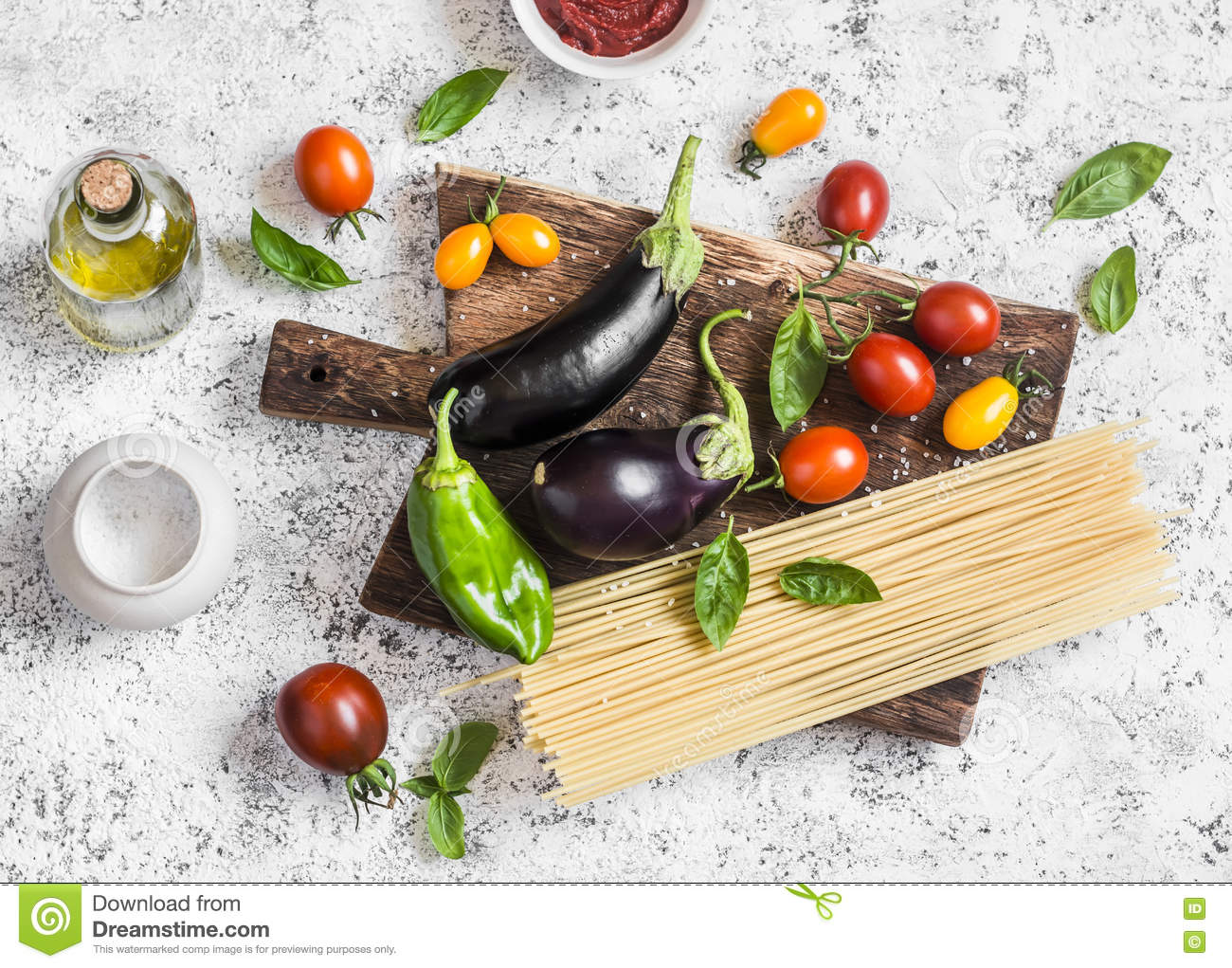 Cooking background. Raw ingredients for making pasta - spaghetti, eggplant, tomatoes, pepper, olive oil, tomato sauce and basil on