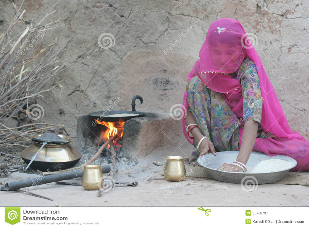 Young African Rural Girl Cooking Lunch In The Open