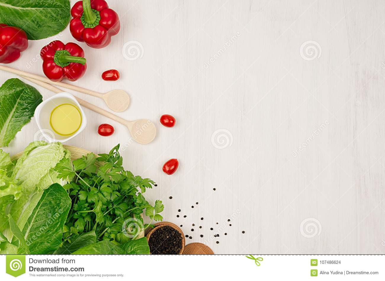 Cooking fresh spring salad of green and red vegetables, spices on white wooden background, border, top view.