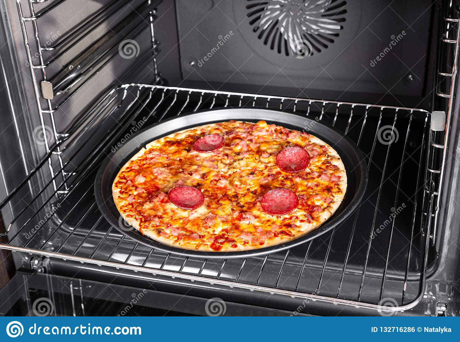 Cooking homemade pizza with salami sausage in an electric oven