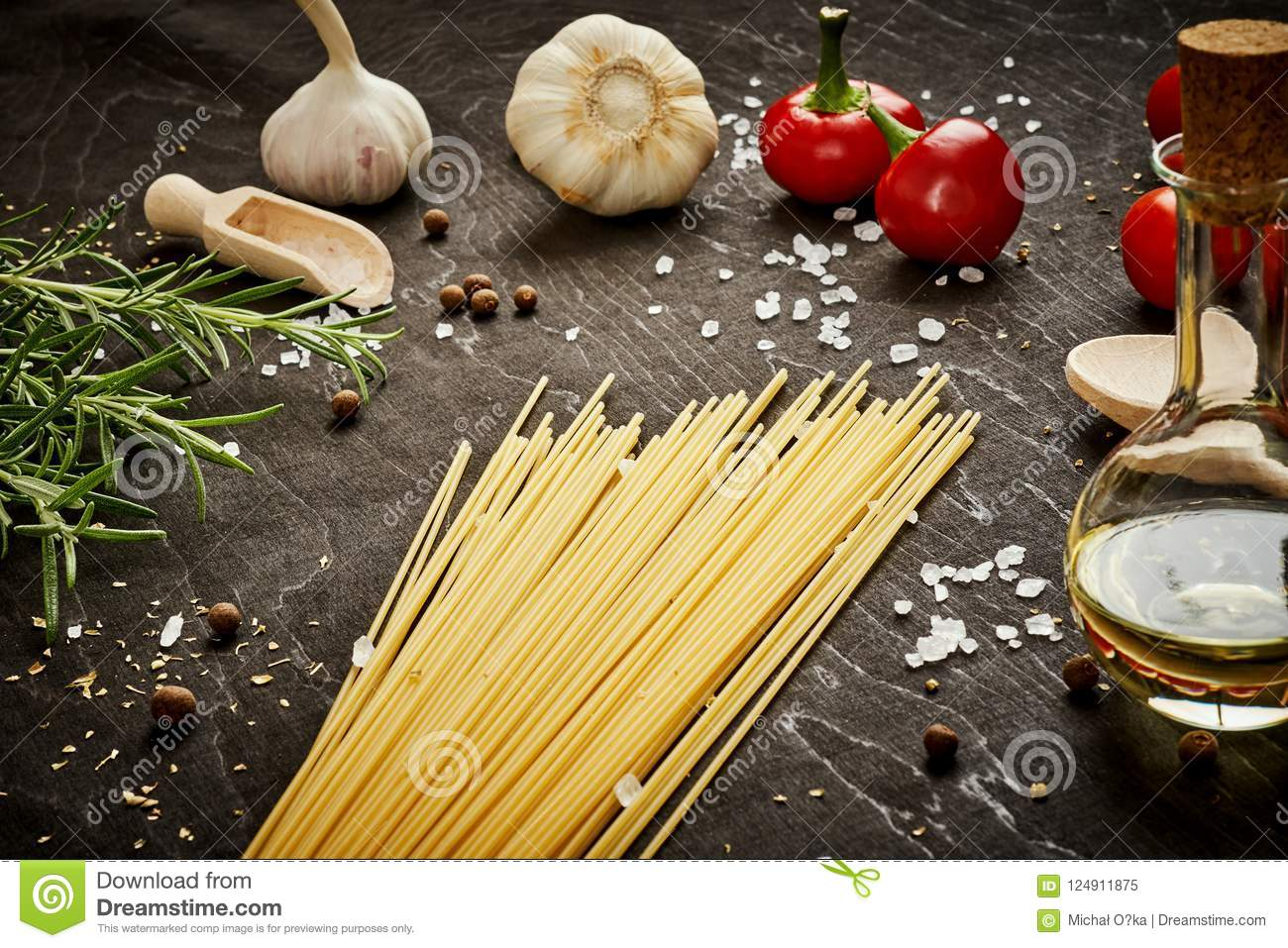Tomatoes garlic salt olive peppers and pasta on a black table