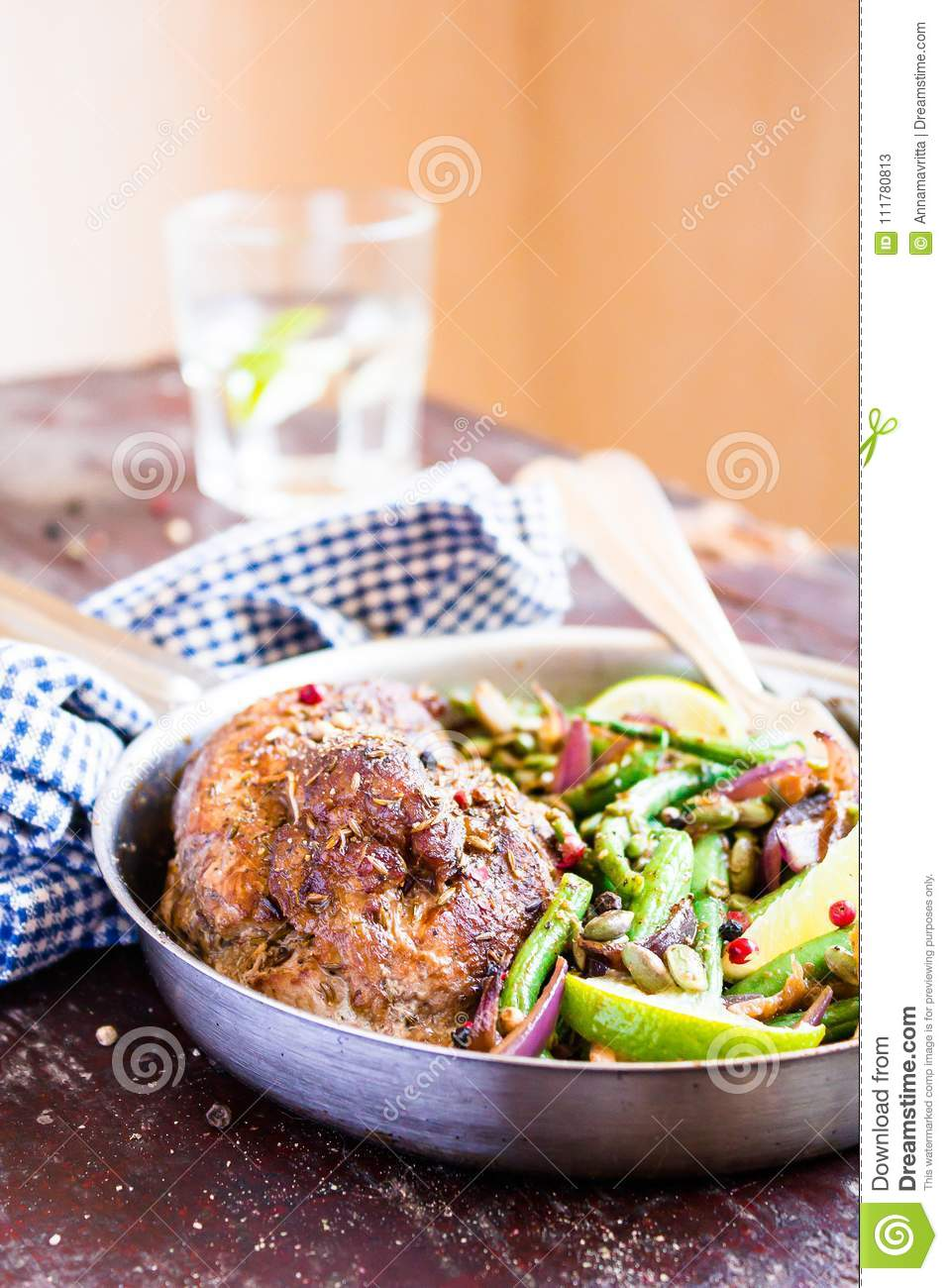 Cooking pan of gourmet meal. Roasted pork loin with spices served with warm salad made from green beans, onion, lime fruit
