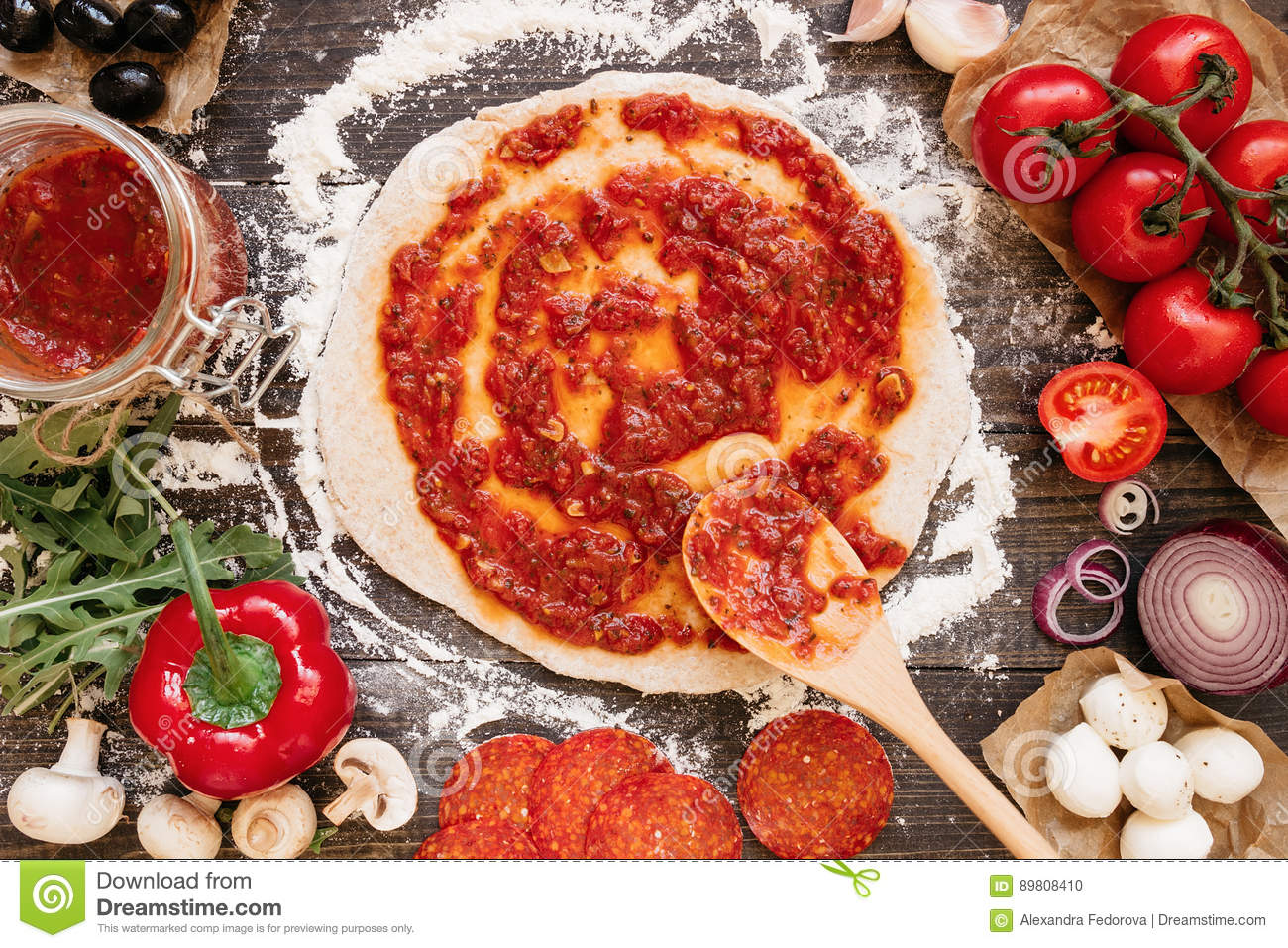 Cooking pizza adding fresh tomato sauce to pizza dough for Table a pizza