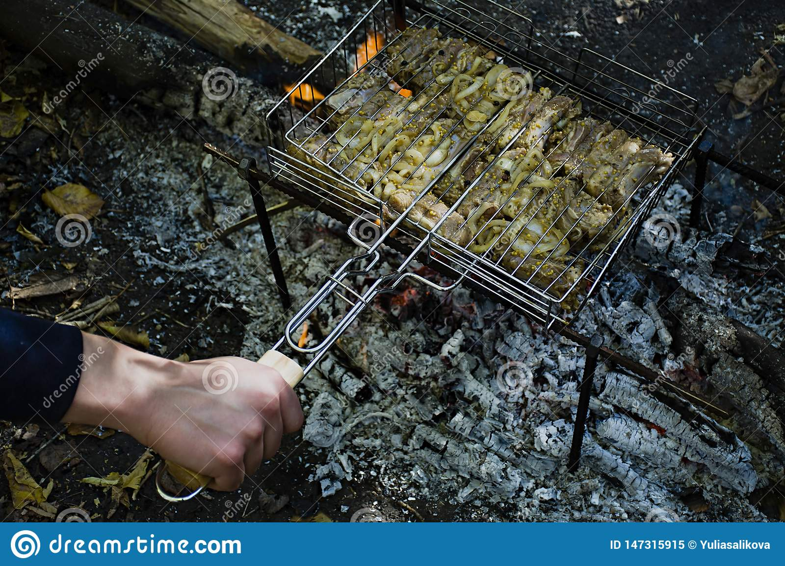 Cooking pork ribs on the fire. Shish kebab on the grill, barbecue with a flame in nature. Side view