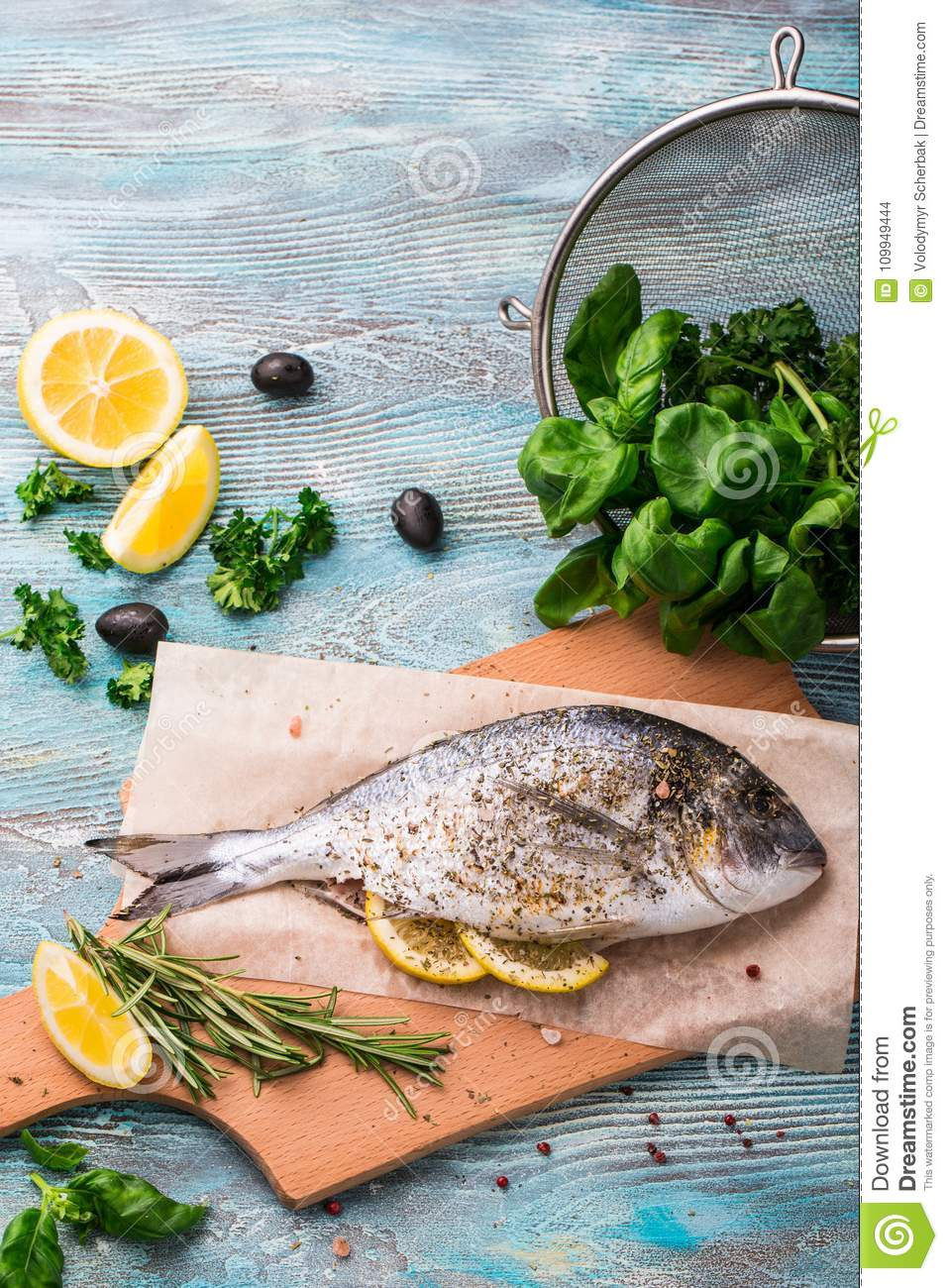 Cooking Raw Dorado Fish With Spinach, Rosemary, Olives, Herbs ...