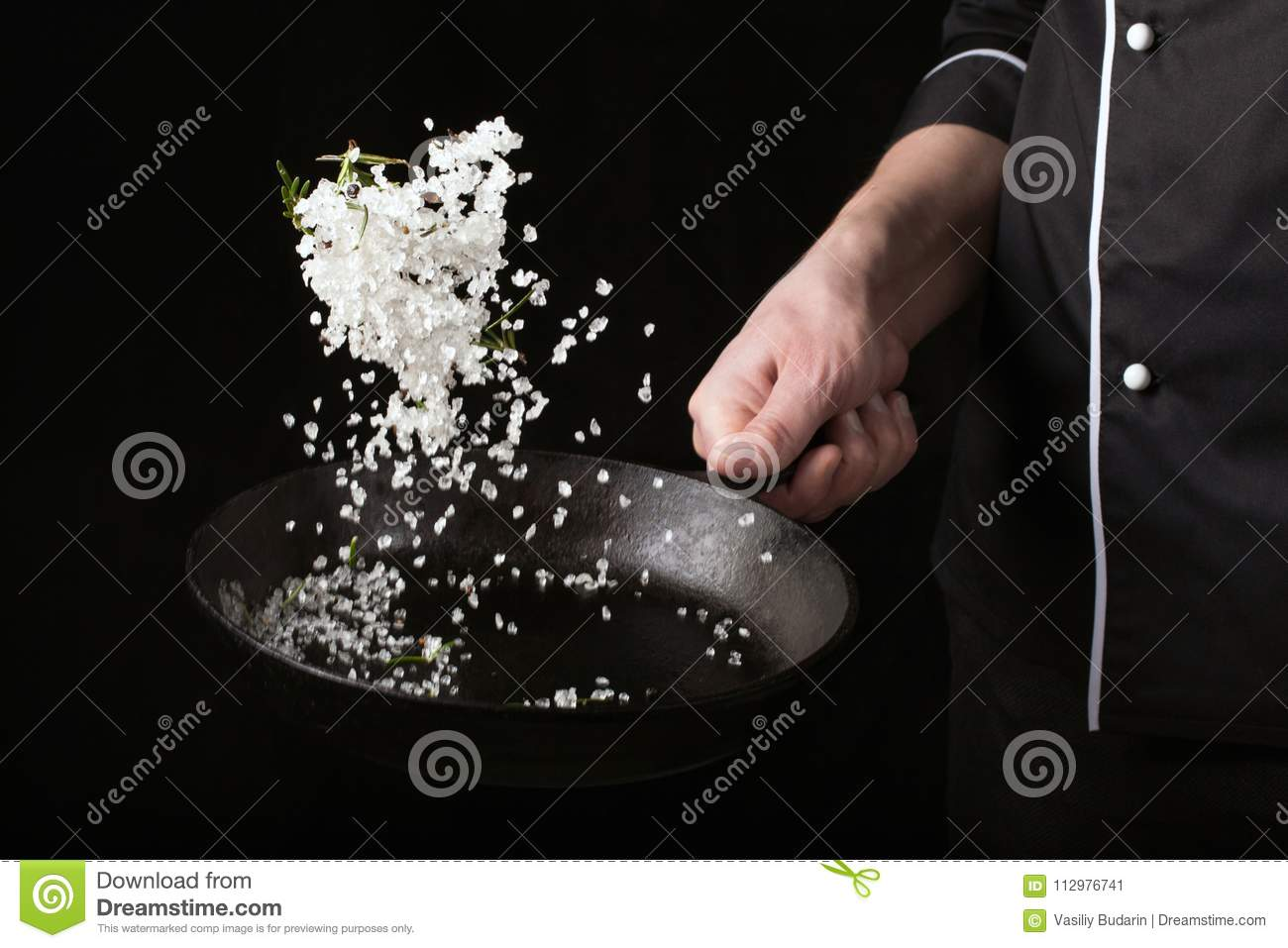 Cooking roasted aromatic salt in a pan by chef hand. Horizontal photo view. Dark black background with copy text area