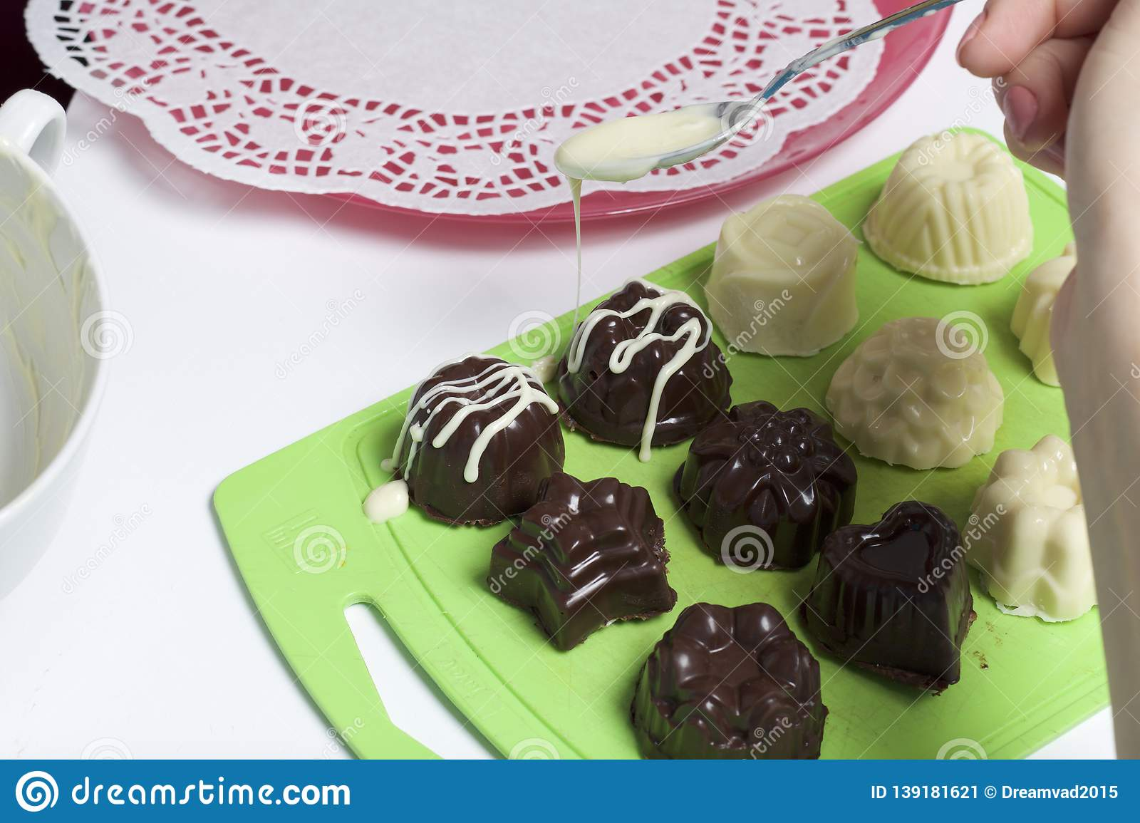 Cooking sweets with coconut and condensed milk. In a glaze of white and black chocolate