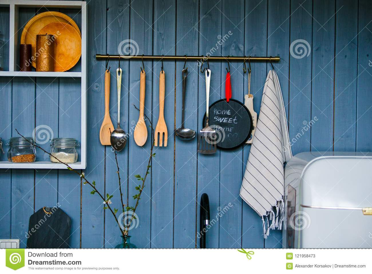 Cooking utensils hanging on wooden wall in the kitchen transparent glass jars for grain