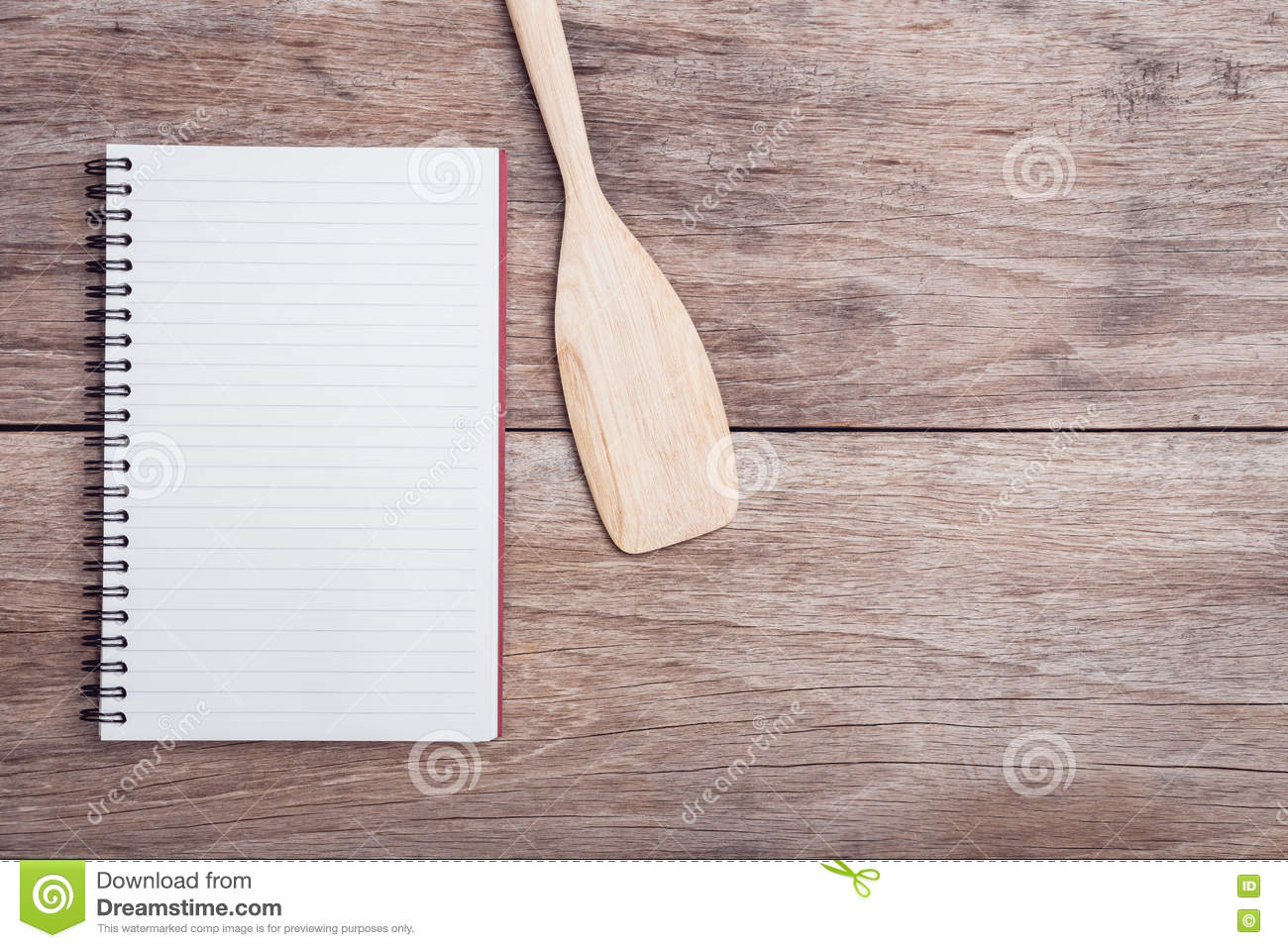 Cooking wooden spatula and lined paper on table top