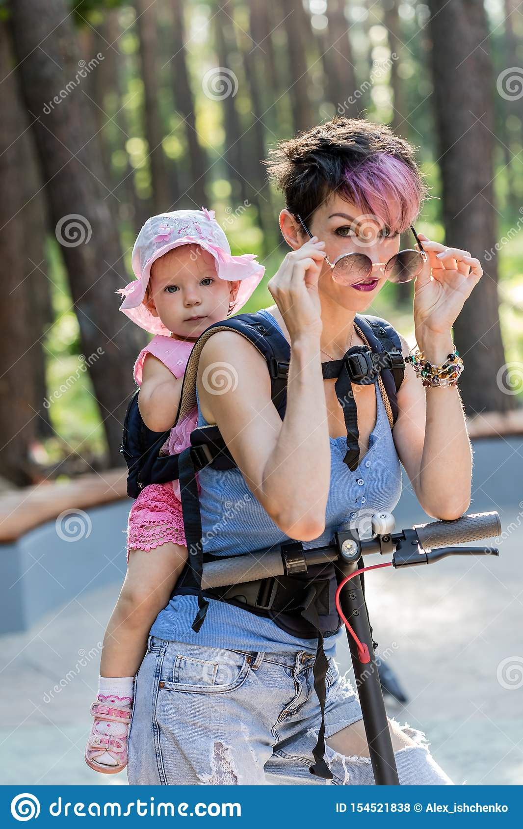 Cool attractive woman enjoys riding an electric scooter with her daughter in sling