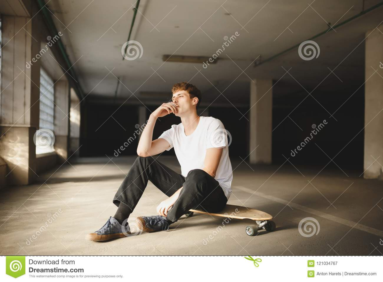 Cool boy with brown hair sitting on skateboard and smoking young thoughtful man in white