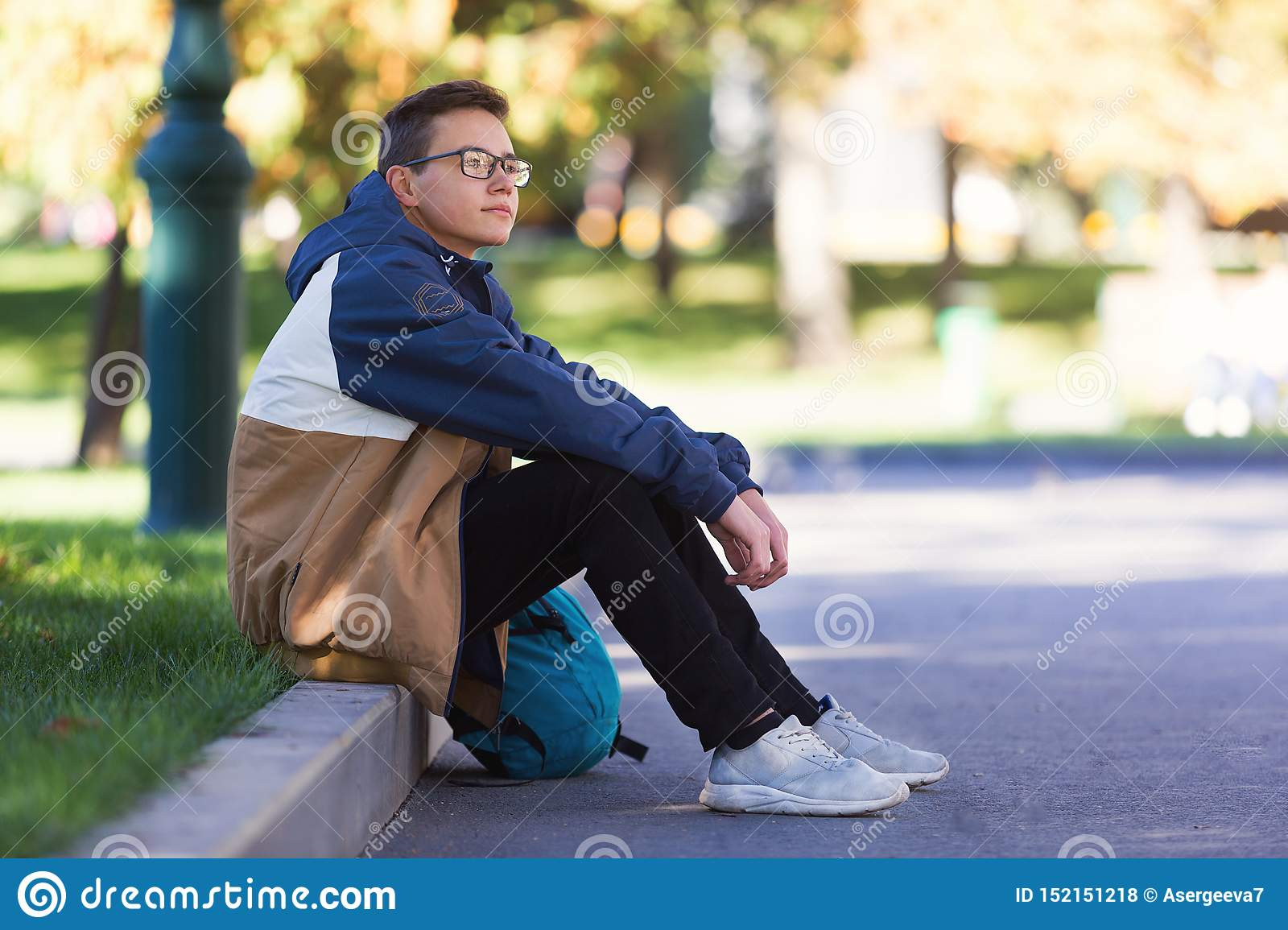 Cool guy sitting and relaxing outdoors during a break in class