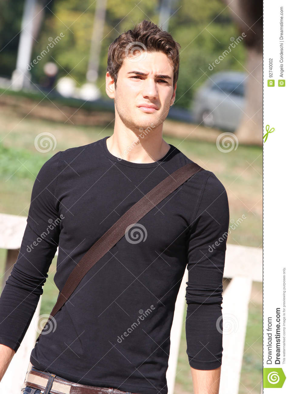 Cool and handsome young man outdoors. Modern hairstyle.