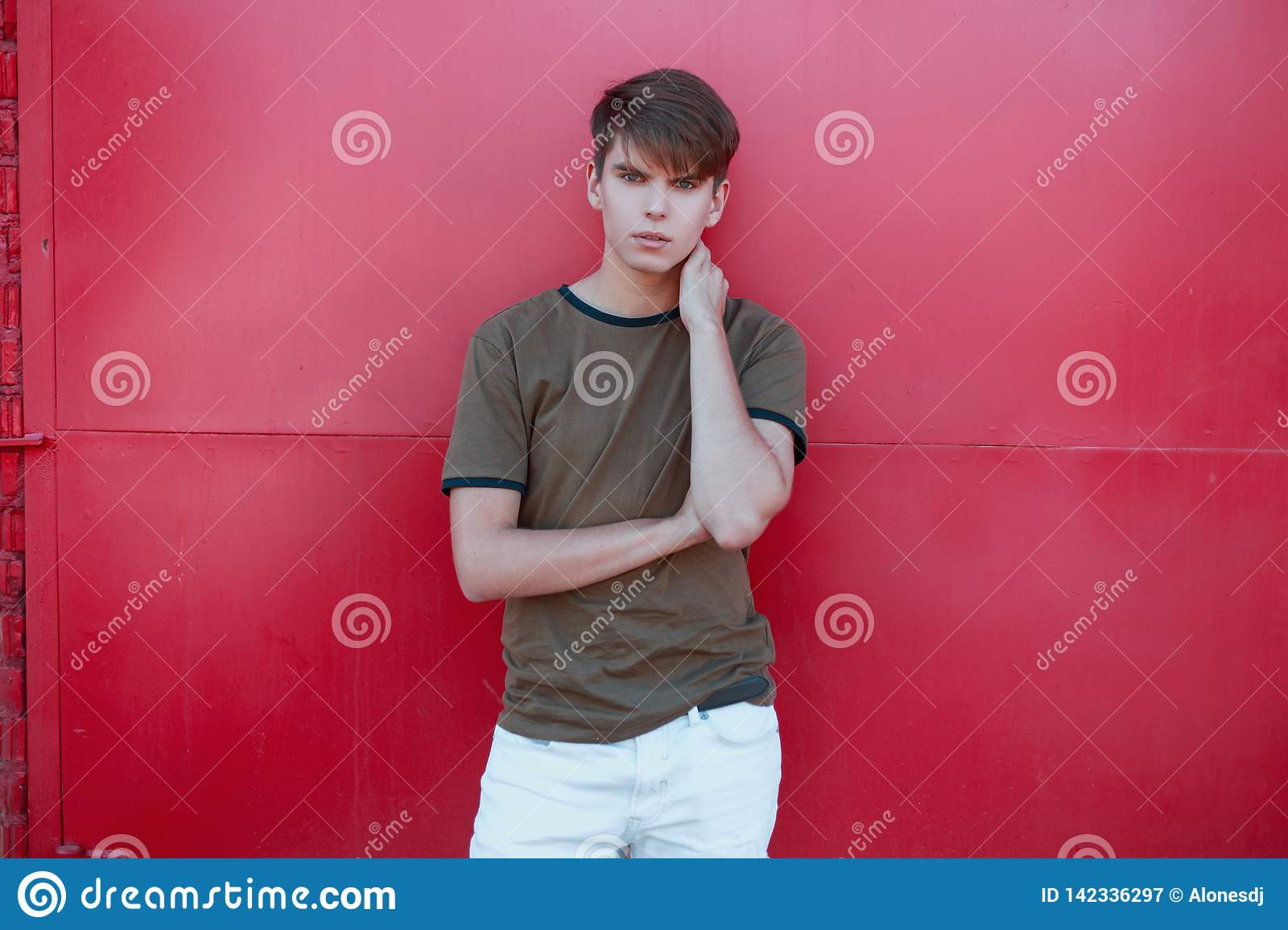 Cool handsome young man with a stylish hairstyle in a trendy green t-shirt in white trousers near the bright pink metal wall