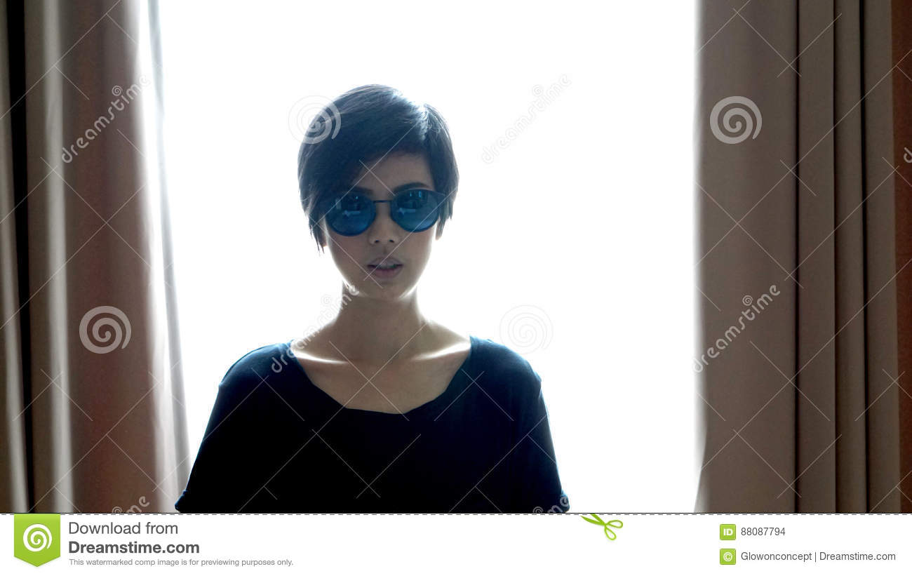 Cool hipster Asian woman wearing sunglasses with backlighting