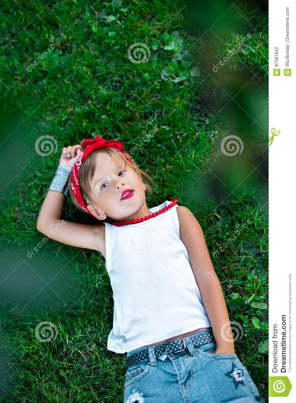 Cool little girl outdoor lying on the grass. Child in white t-shirt, jeans shorts, red necklace and bandage on the head. Summer.