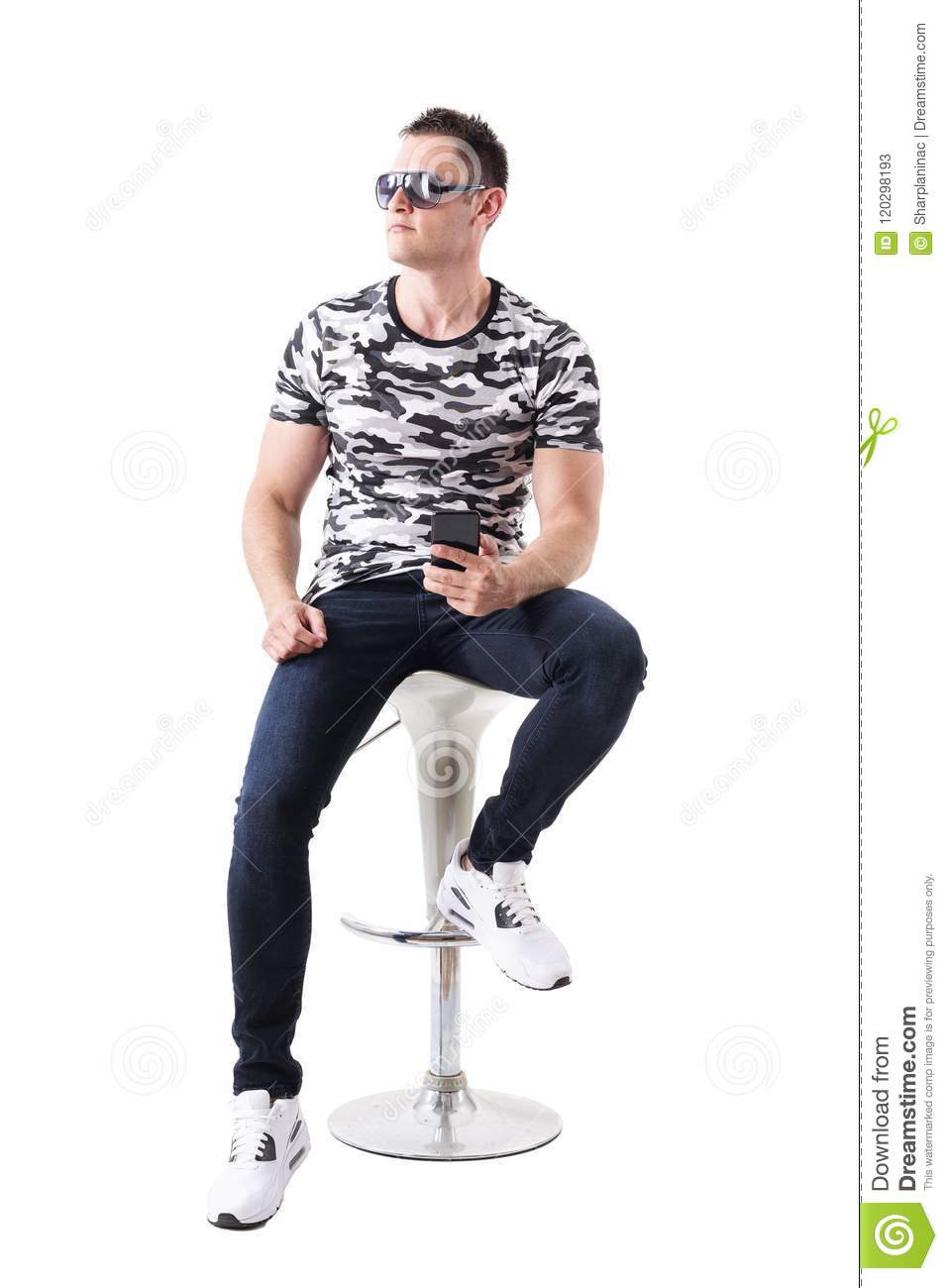 b62ef93a Cool man wearing sunglasses and camouflage t-shirt holding mobile phone  looking away sitting on bar stool.