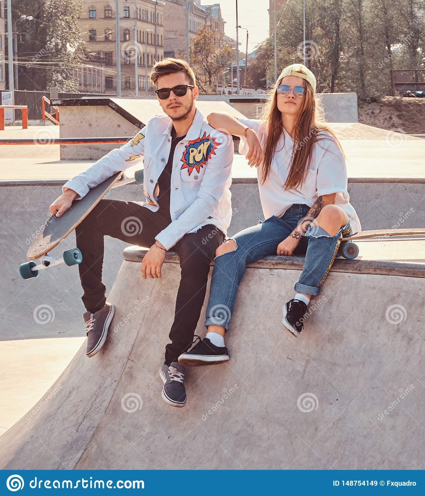 Cool trendy students are sitting at sunny skatepark with their longboards