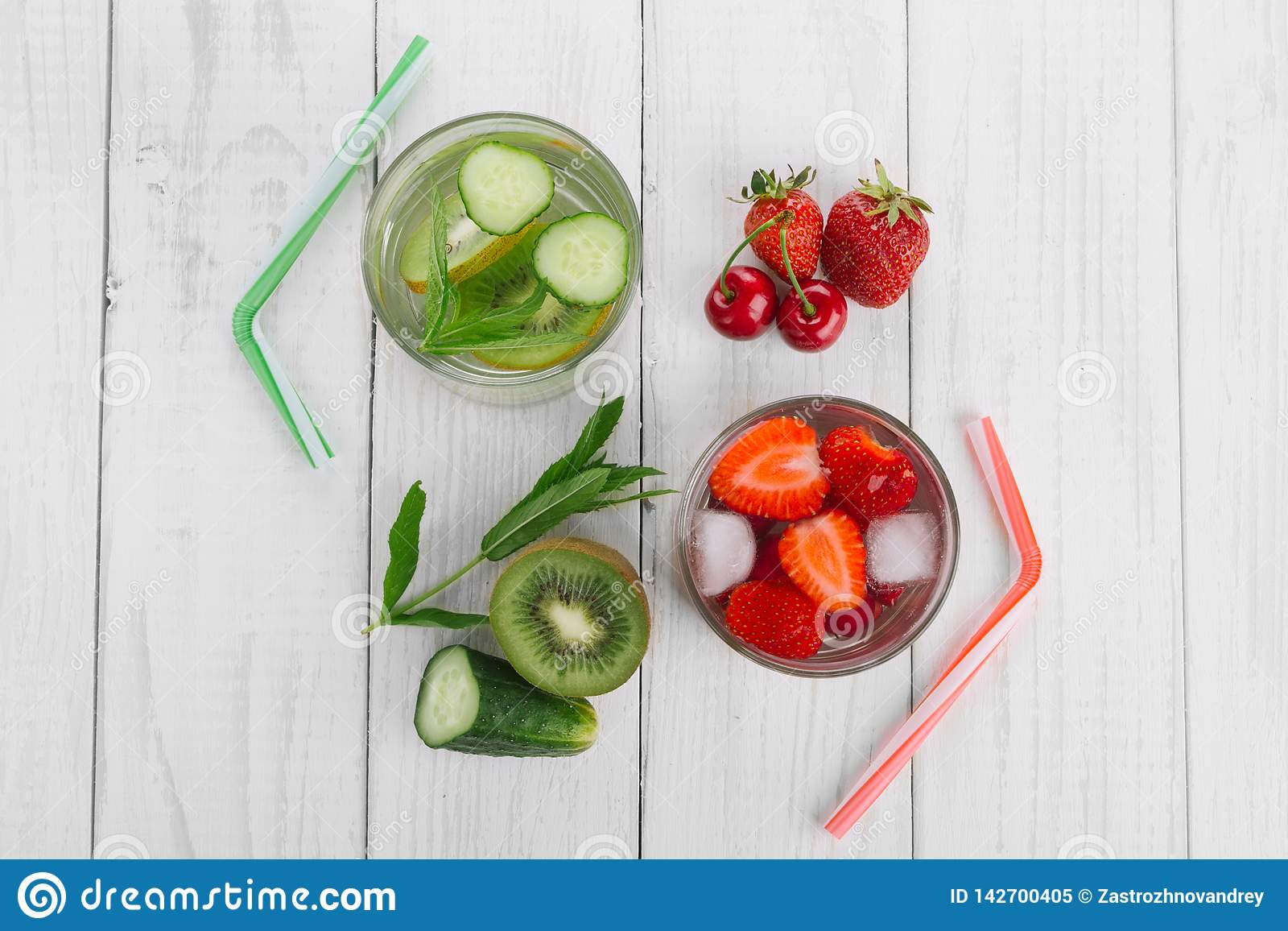 Cool water in glass, fresh green kiwi, mint and cucumber, strawberries and cherries. Fresh homemade vitamins