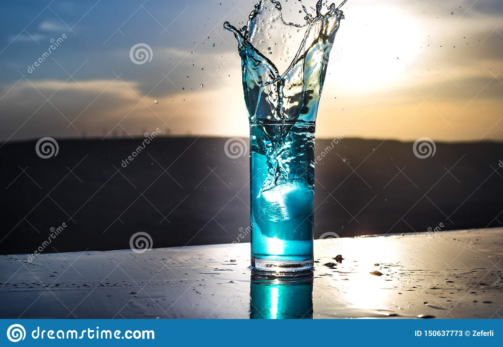 Cooling summer drink concept. Cocktail glasses splashing on sunset. Close up wet glass of cold drink on the terrace