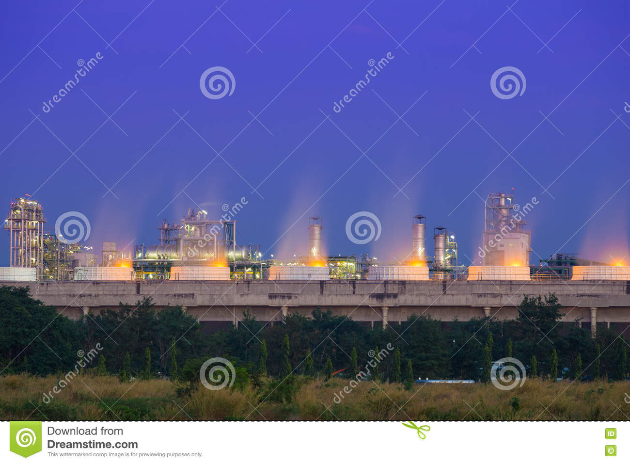 Cooling tower of oil refinery industrial plant at night, Thailand