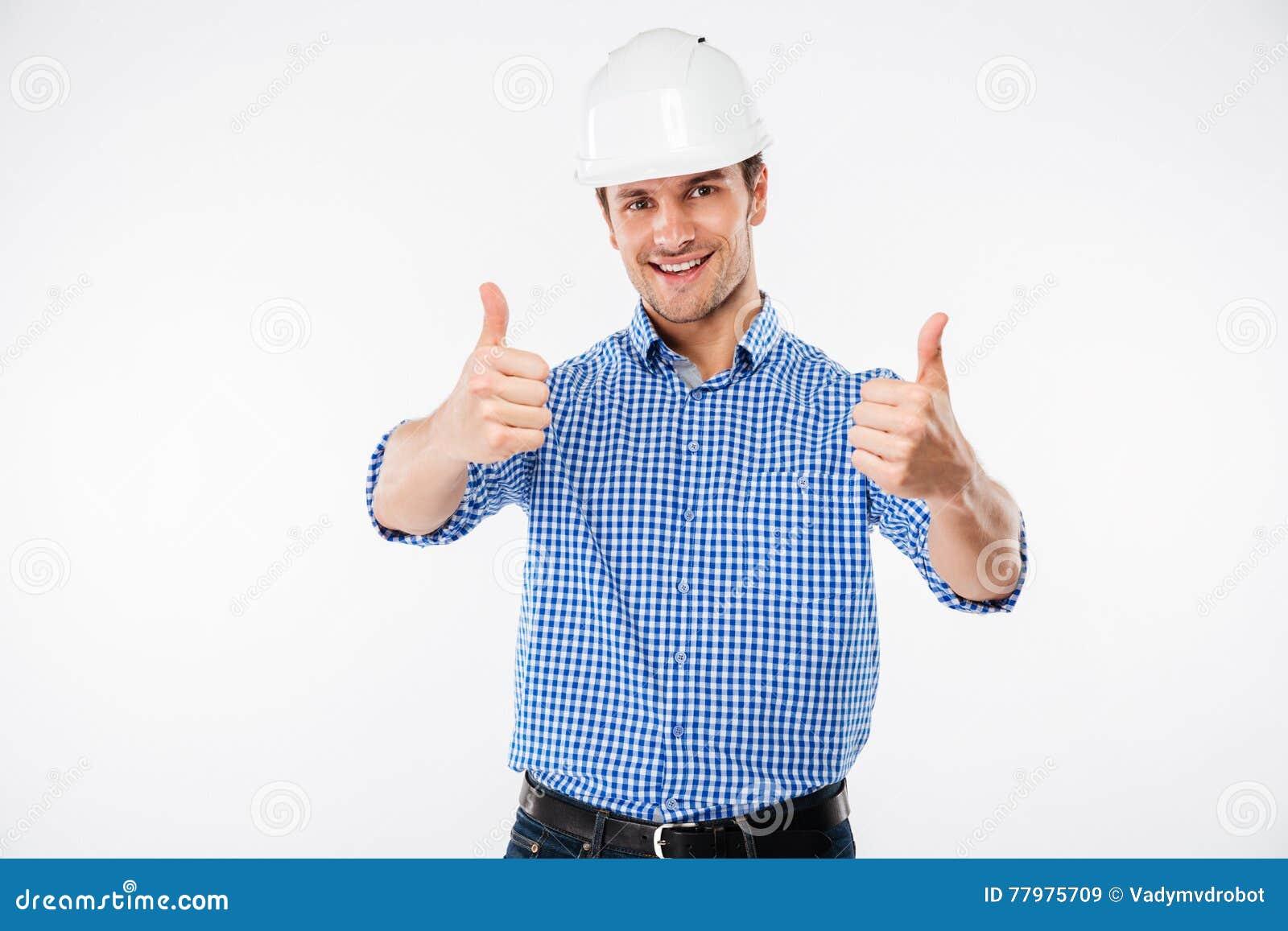 Coordenador alegre do homem novo no capacete da construção que mostra os polegares acima