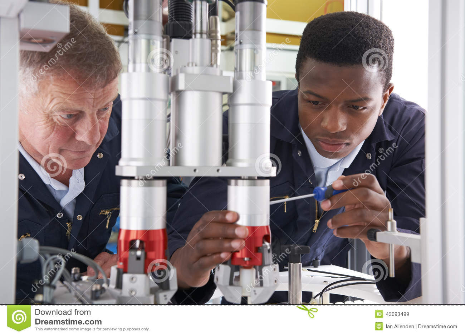 Coordenador And Apprentice Working na máquina na fábrica