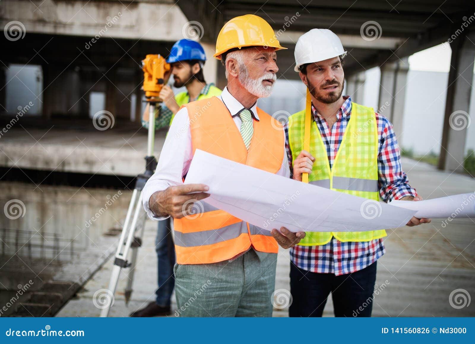 Coordenador, contramestre e trabalhador discutindo no local da construção civil