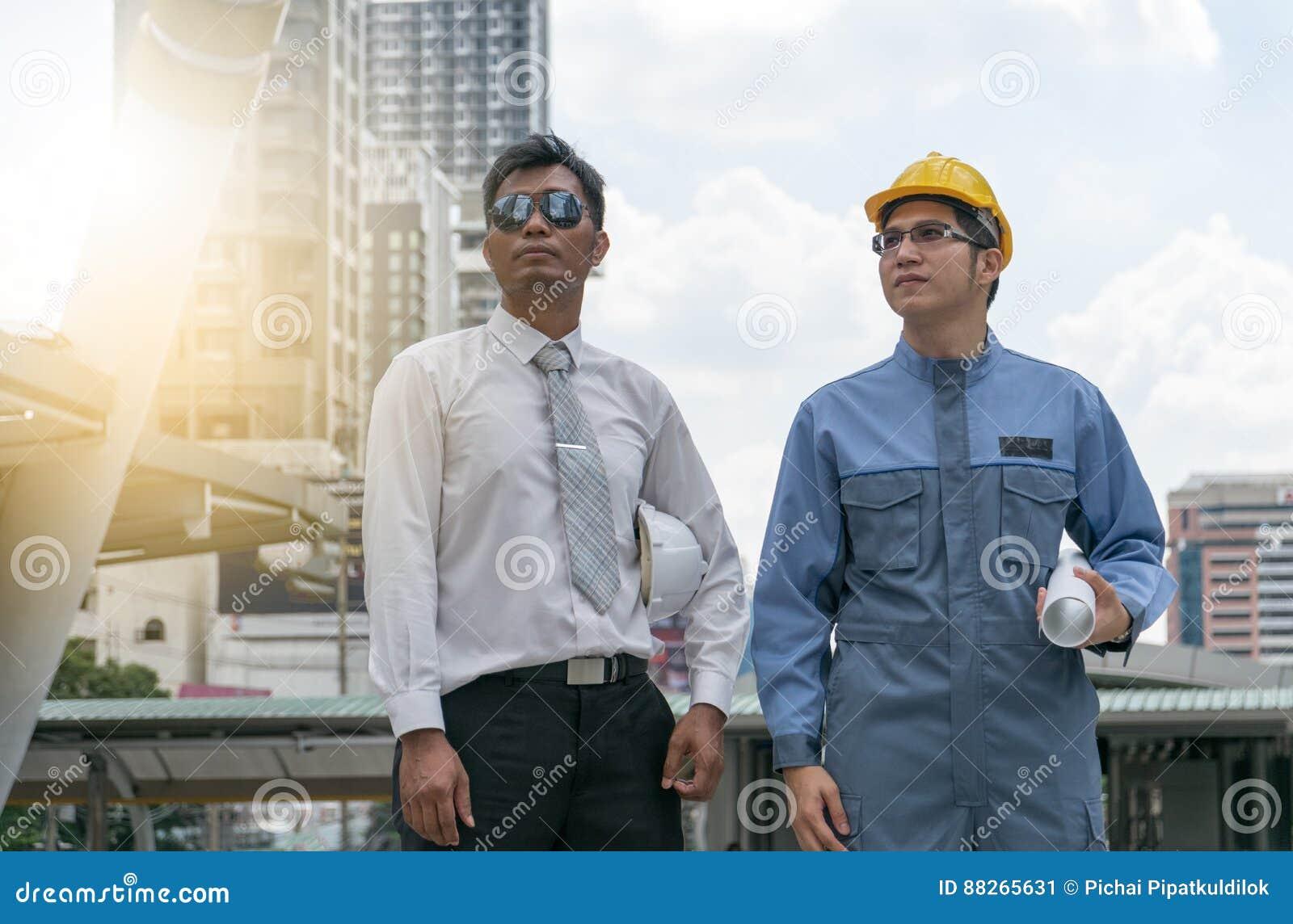 Coordenador e arquiteto que trabalham no canteiro de obras com bluepri