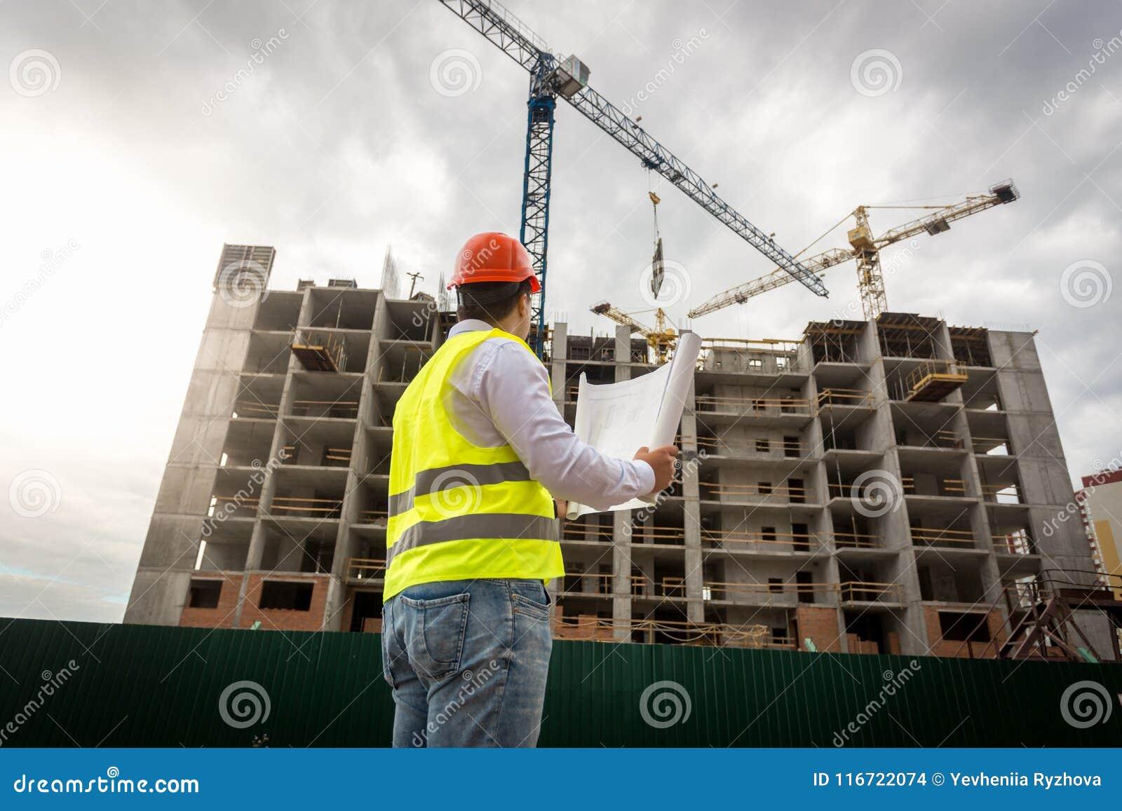 Coordenador masculino na veste e no capacete de segurança da segurança que olham a construção da construção nova
