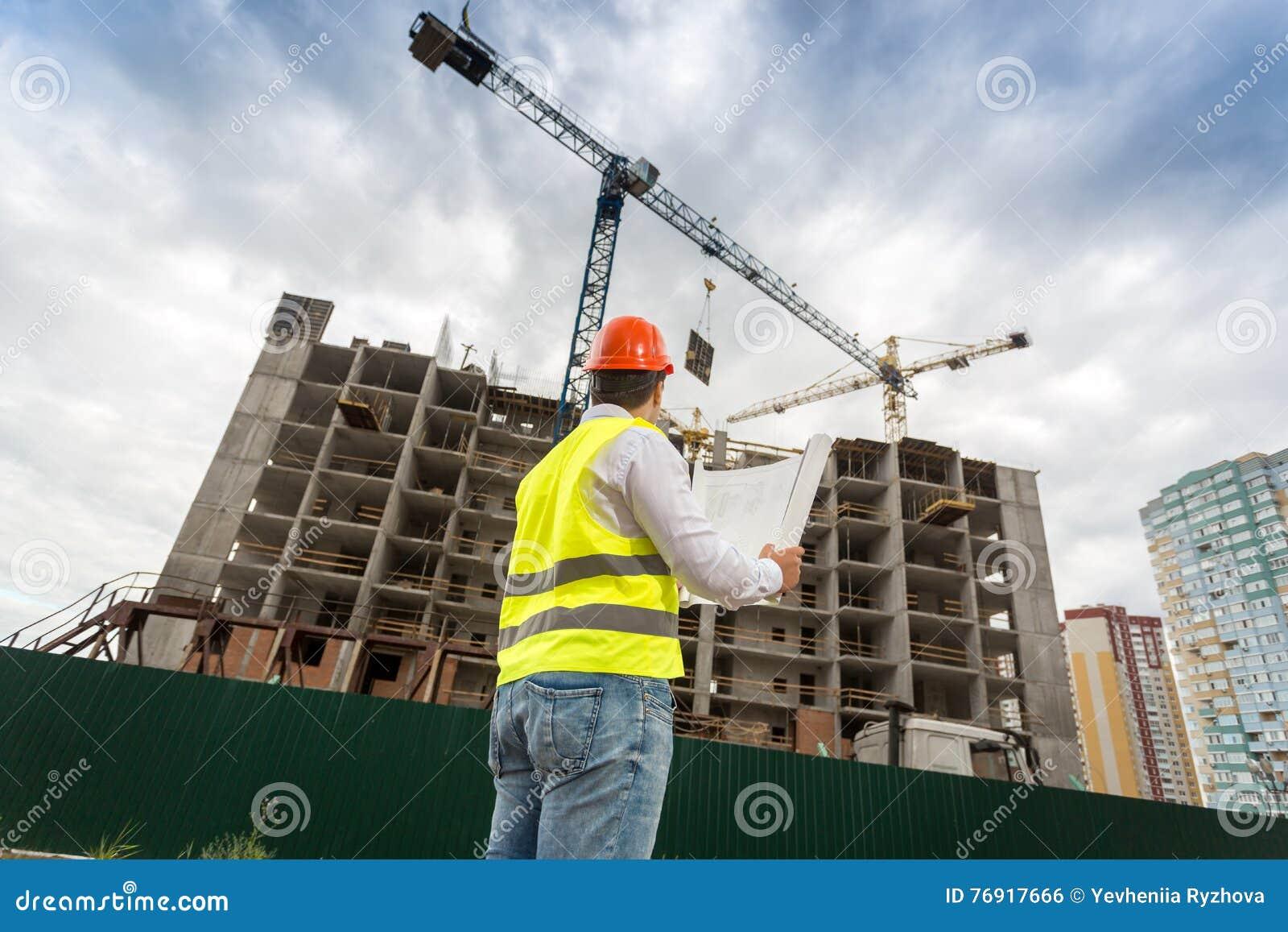 Coordenador no capacete de segurança que olha a construção sob a construção