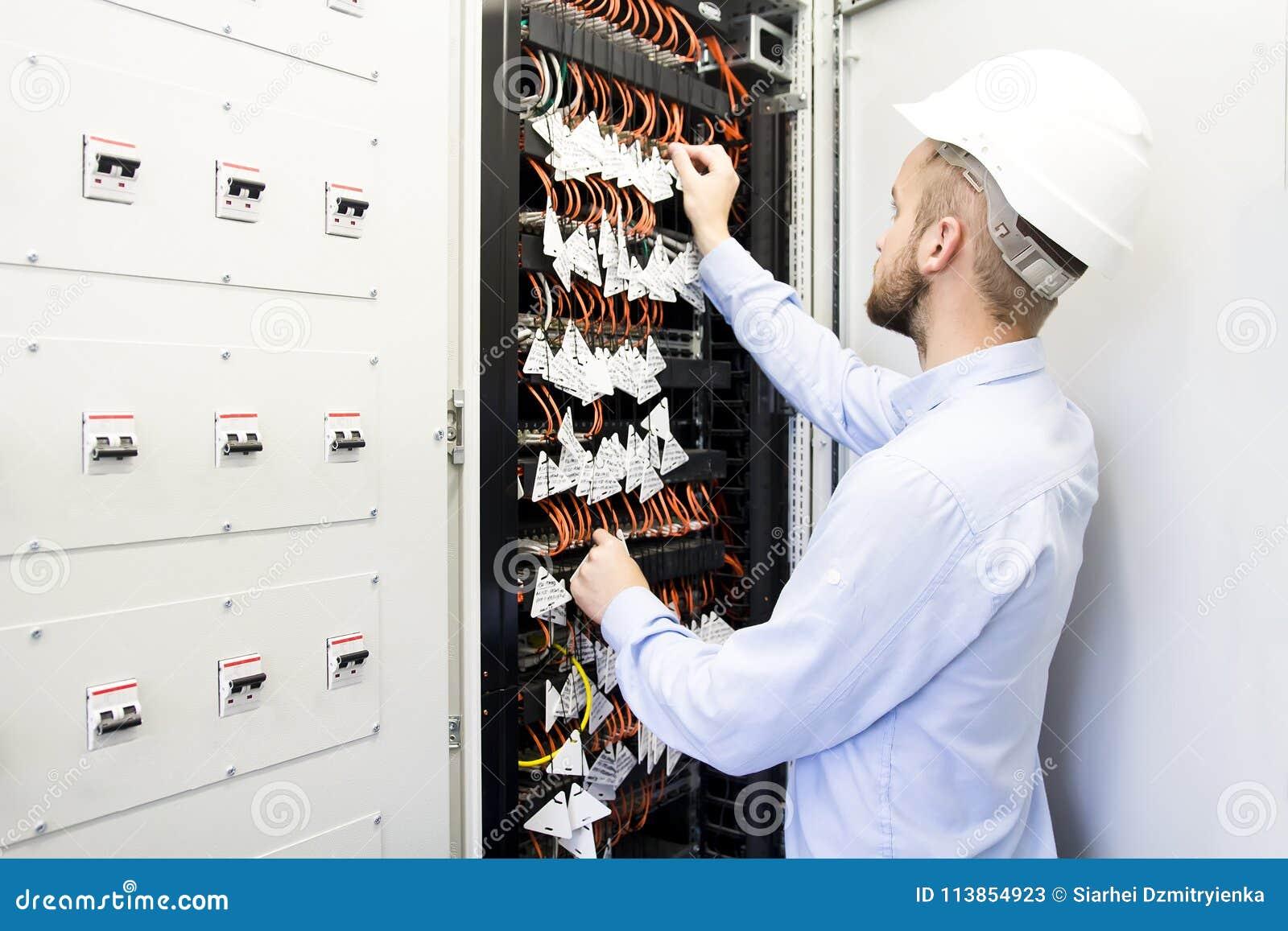 Coordenador no centro de dados Trabalhador em um capacete perto dos interruptores de cabos óticos