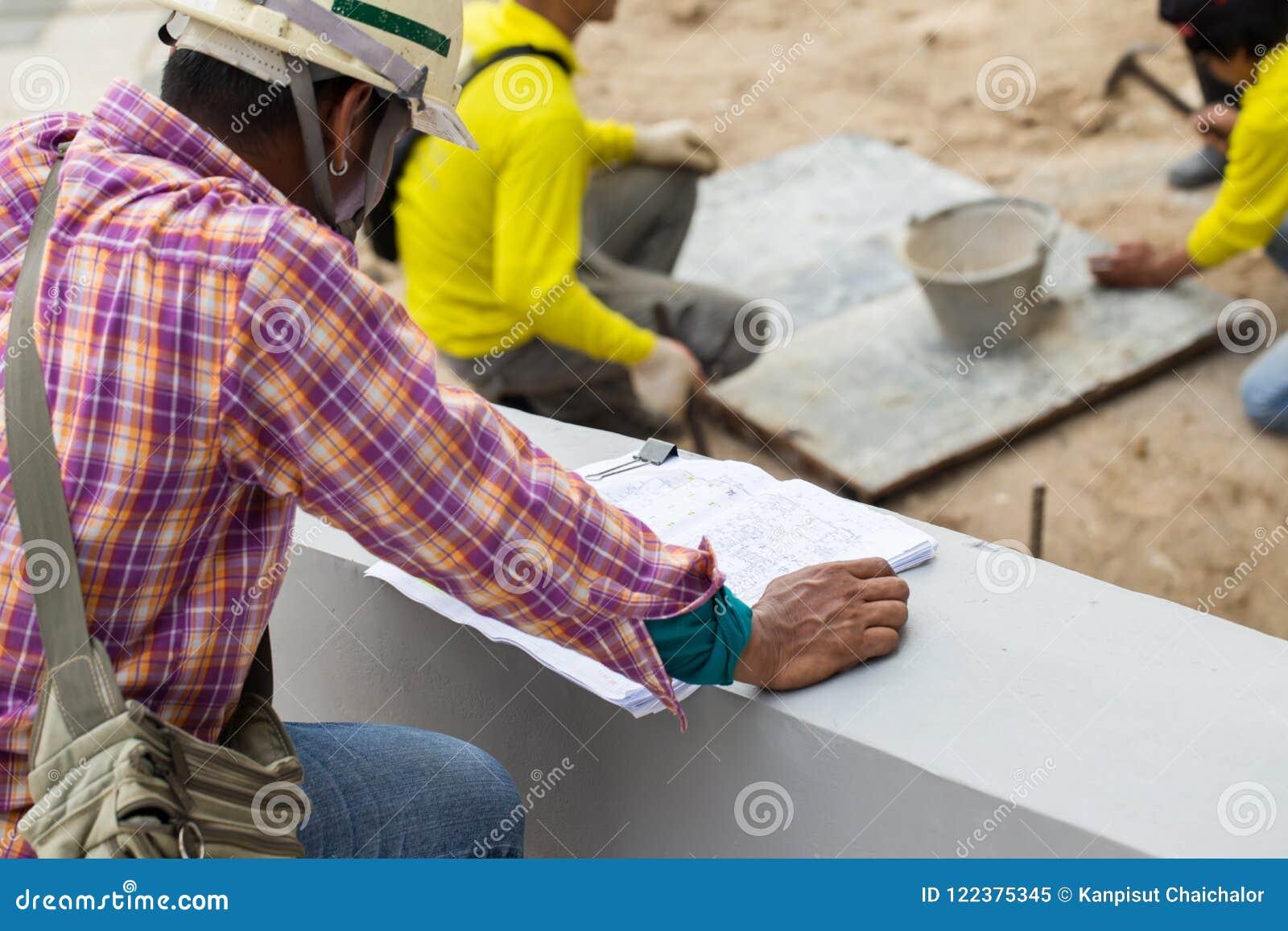 Coordenadores no terreno de construção que verificam planos Coordenador ou arquiteto do plano da construção para a construção no