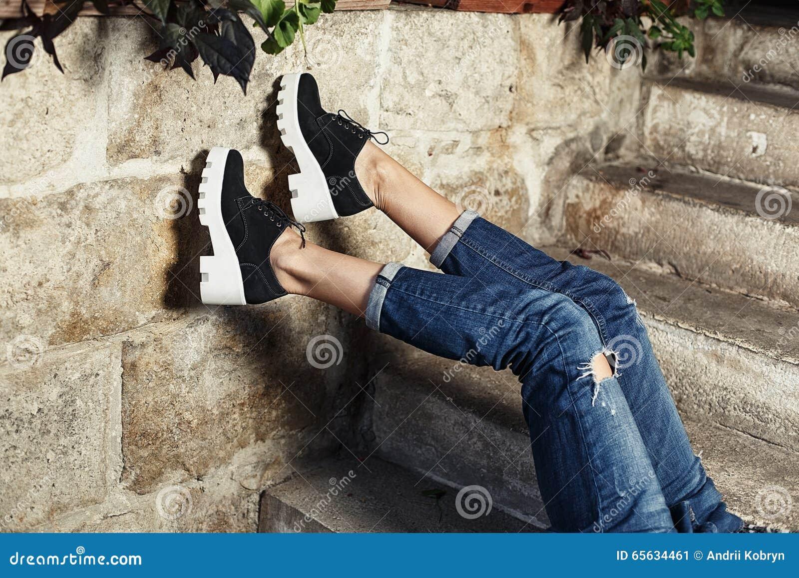 Coordonnée d une jeune fille dans des jeans posant dans un contexte urbain