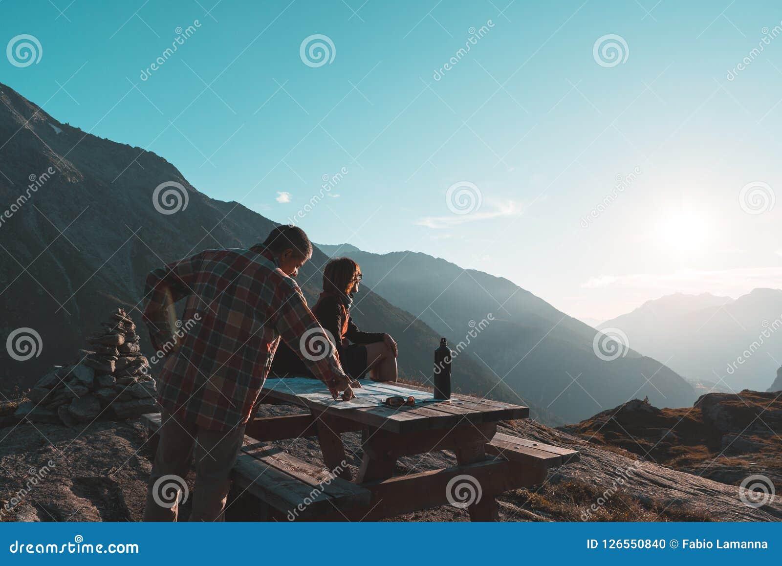 Coouple wycieczkowicze czyta trekking mapę na stole w backlight, tylni widok Przygody eksploracja na Alps