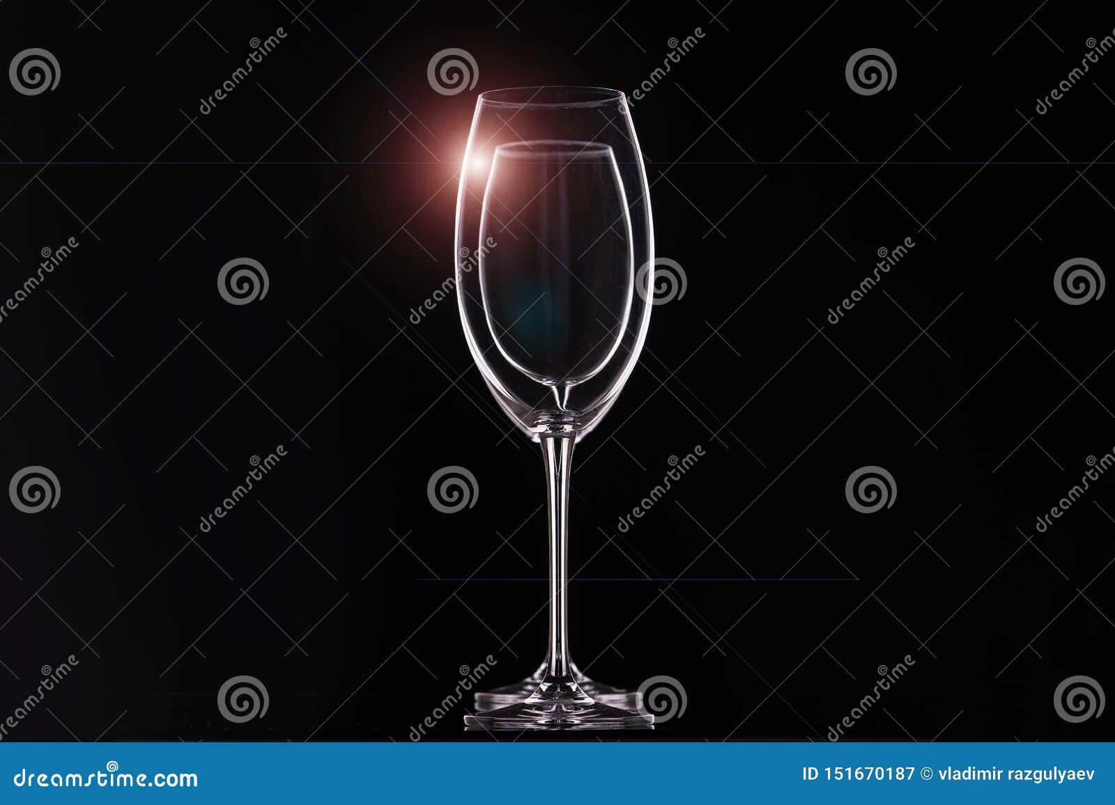 Copas de vino vacías en el fondo negro, cristalería para las bebidas Contornos y resplandor ligero, arreglo horizontal