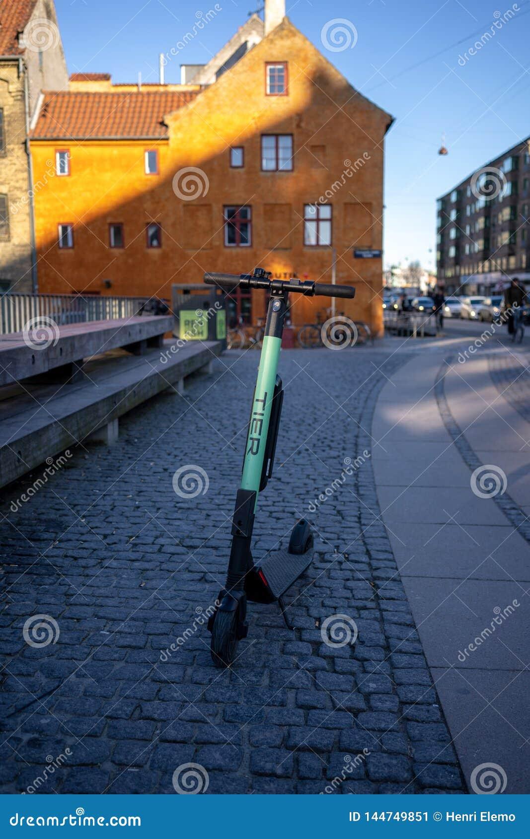 Copenhagen, Denmark - April 1, 2019: Electric scooter from Tier in Copenhagen on morning sun, next to iconic houses in Copenhagen