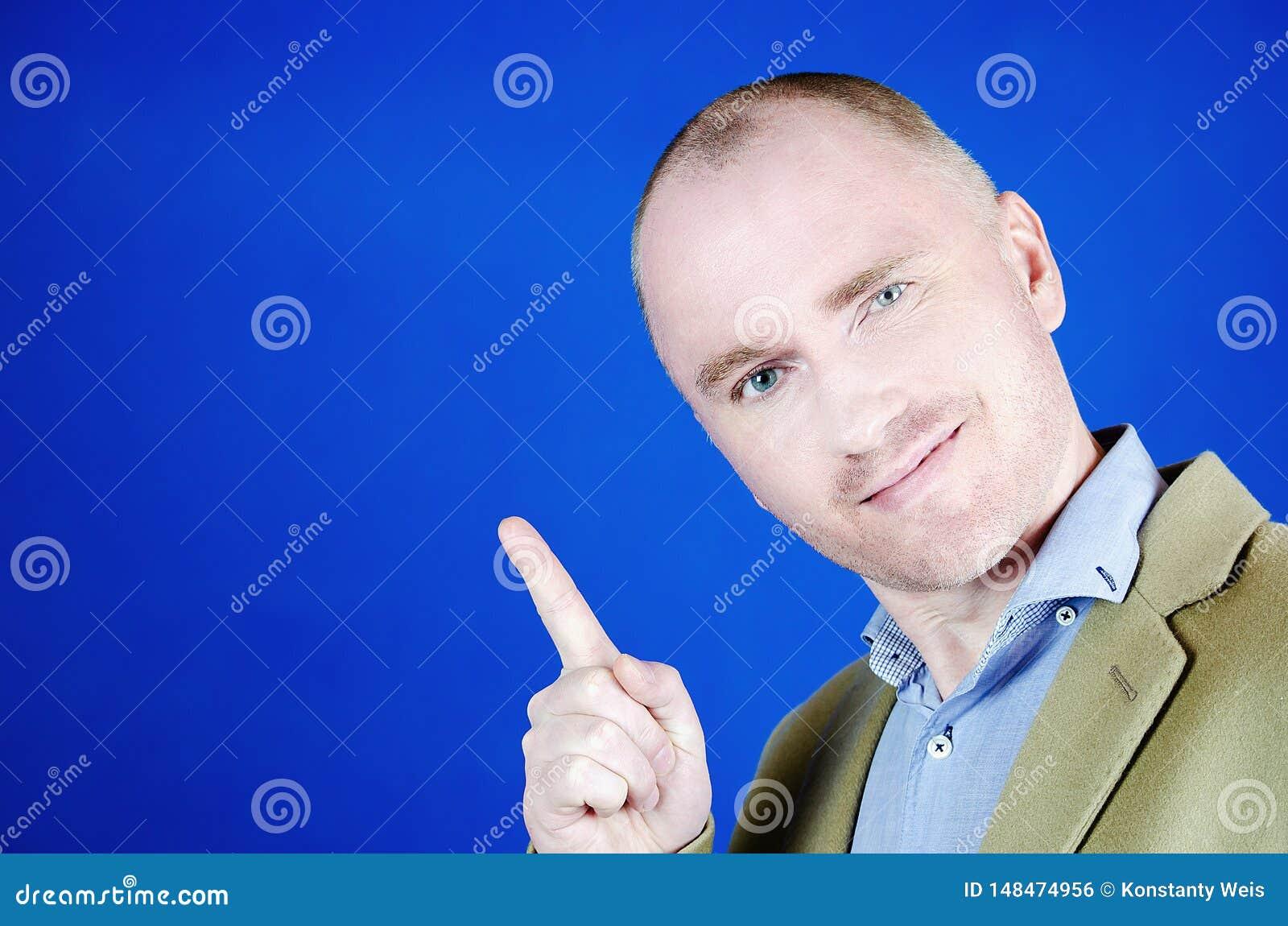 Copie o espa?o em sua m?o Homem maduro feliz no revestimento de creme que aponta o espaço da cópia e a posição de sorriso do quan