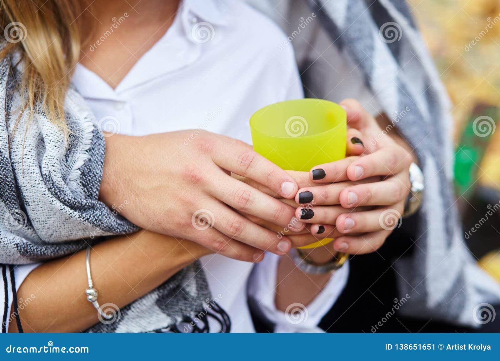Copo amarelo do chá quente nas mãos do amante Pares novos