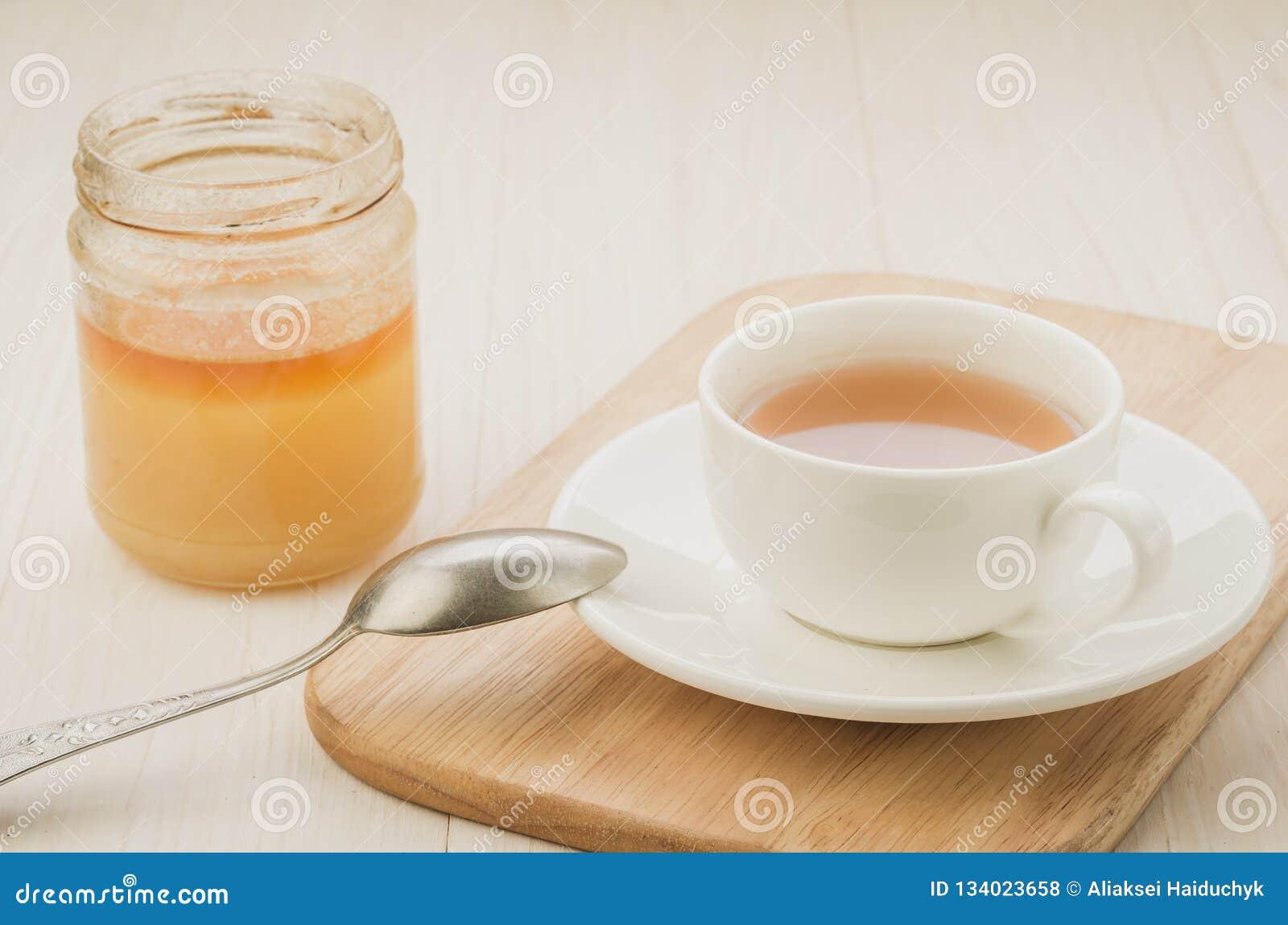 Copo branco do chá com um frasco aberto do mel/copo branco do chá com