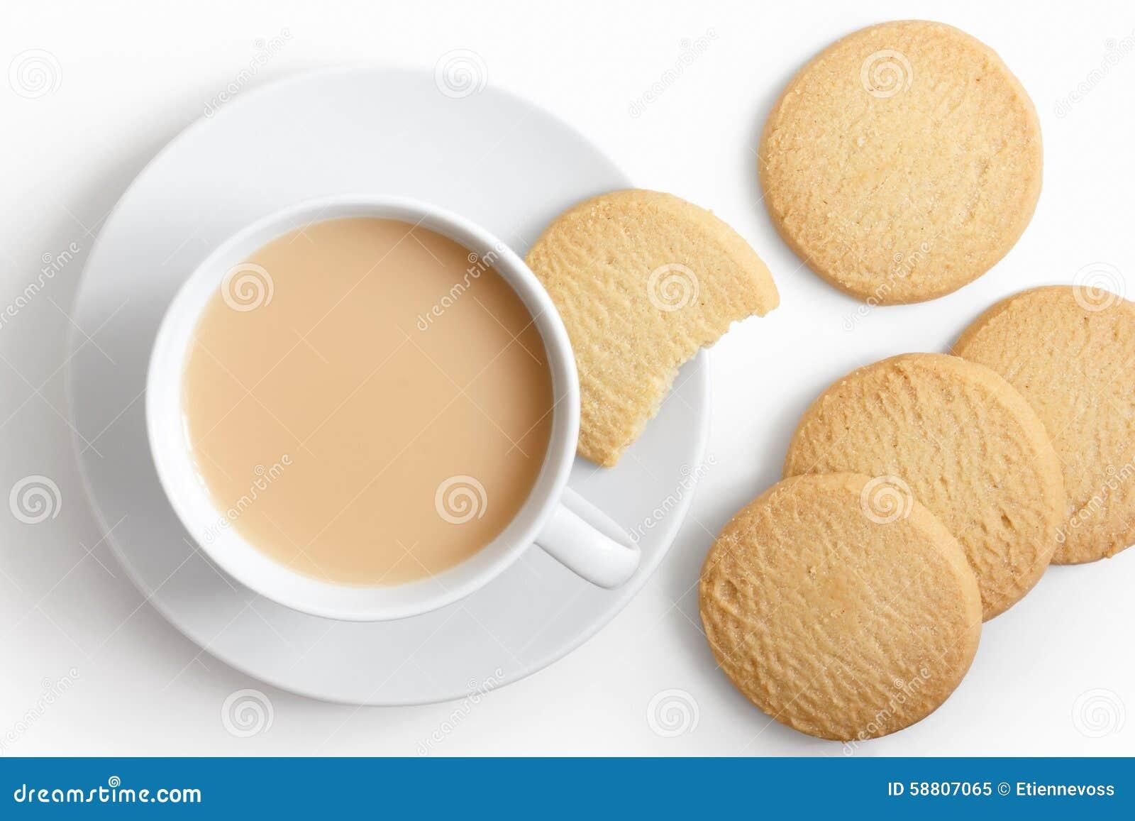 Copo branco do chá e pires com os biscoitos do biscoito amanteigado de cima de
