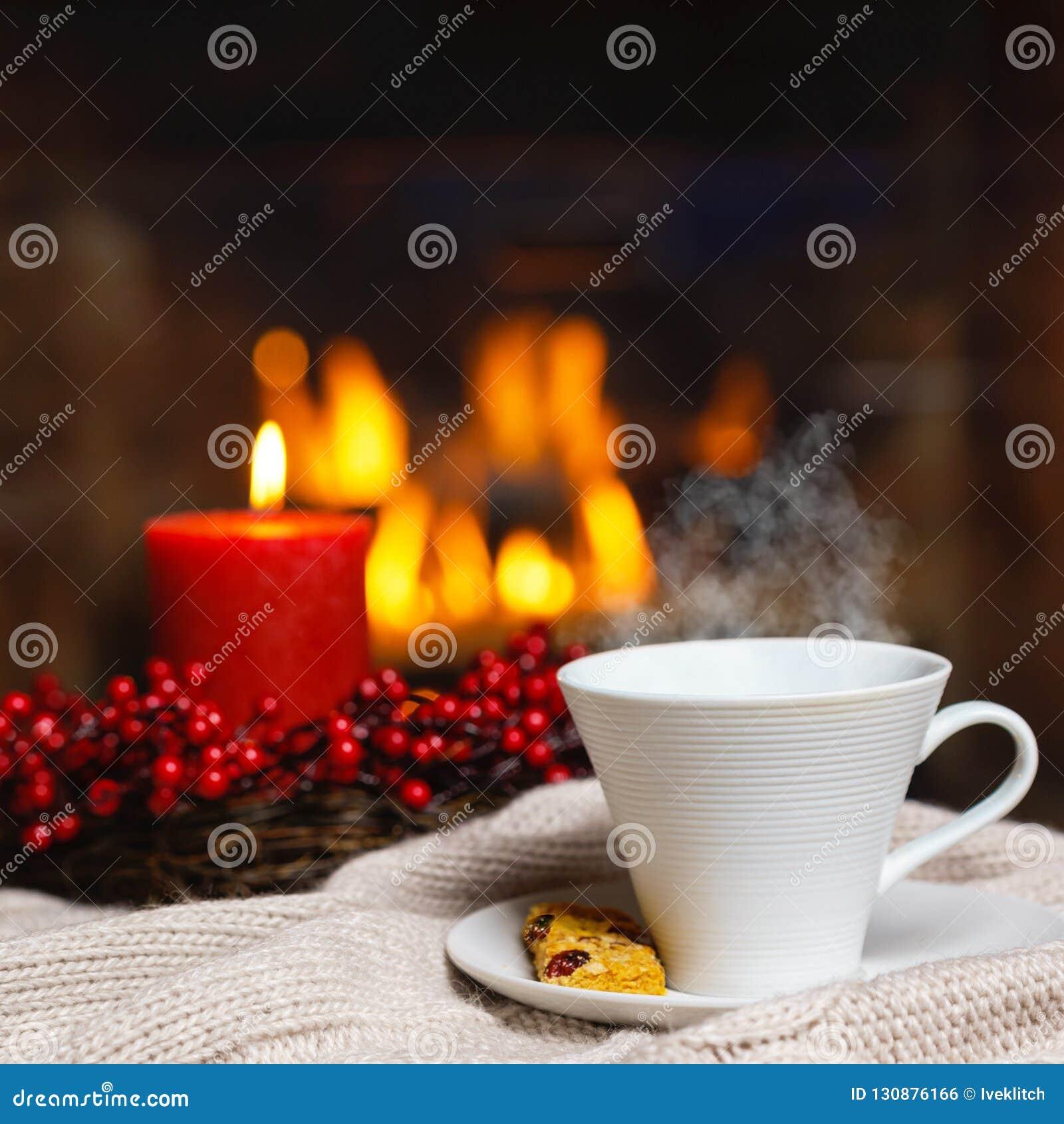 Copo da bebida quente com vela vermelha das bagas do vapor e da cookie em Chr