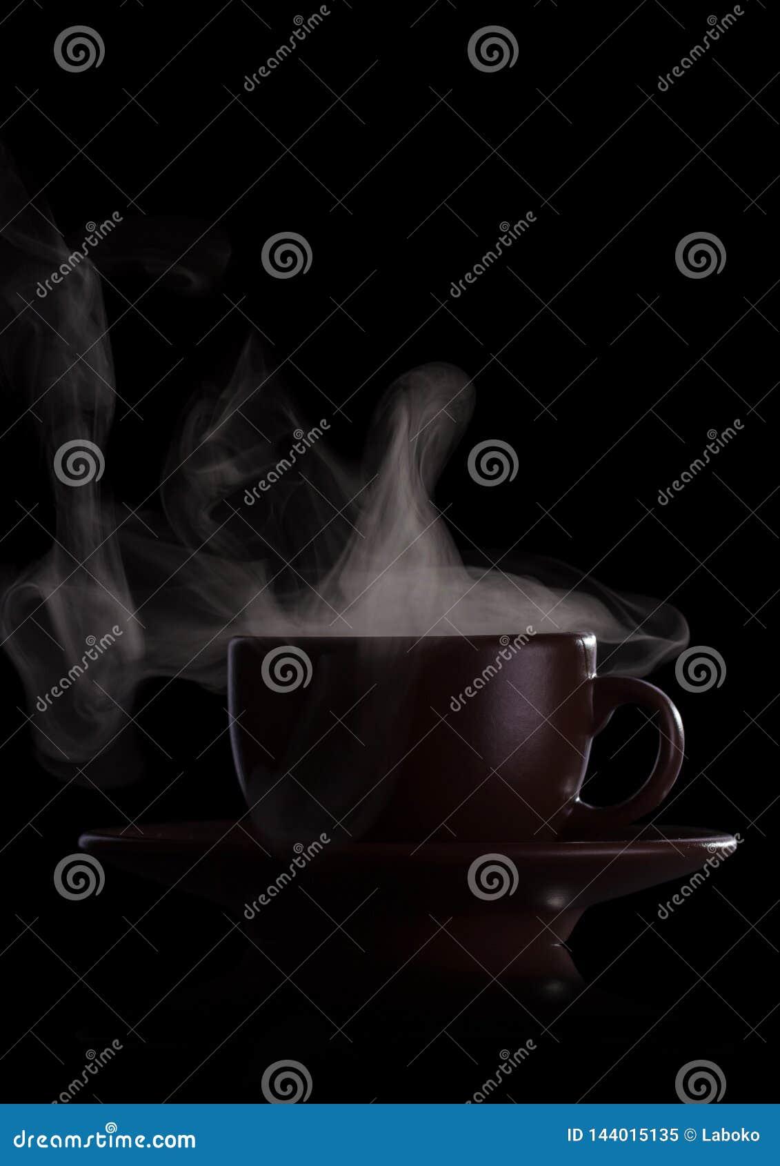 Copo da bebida quente perfumada com o vapor isolado no preto
