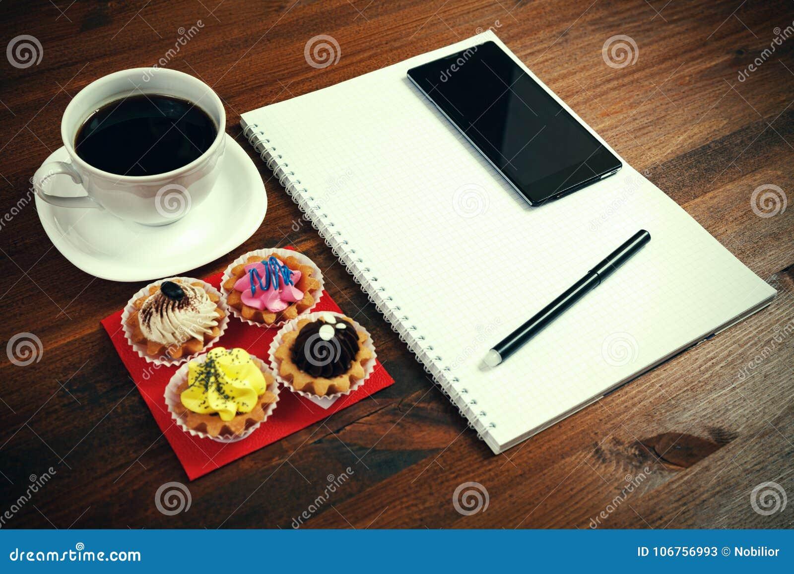 Copo de café branco com caderno, quatro queques, smartphone