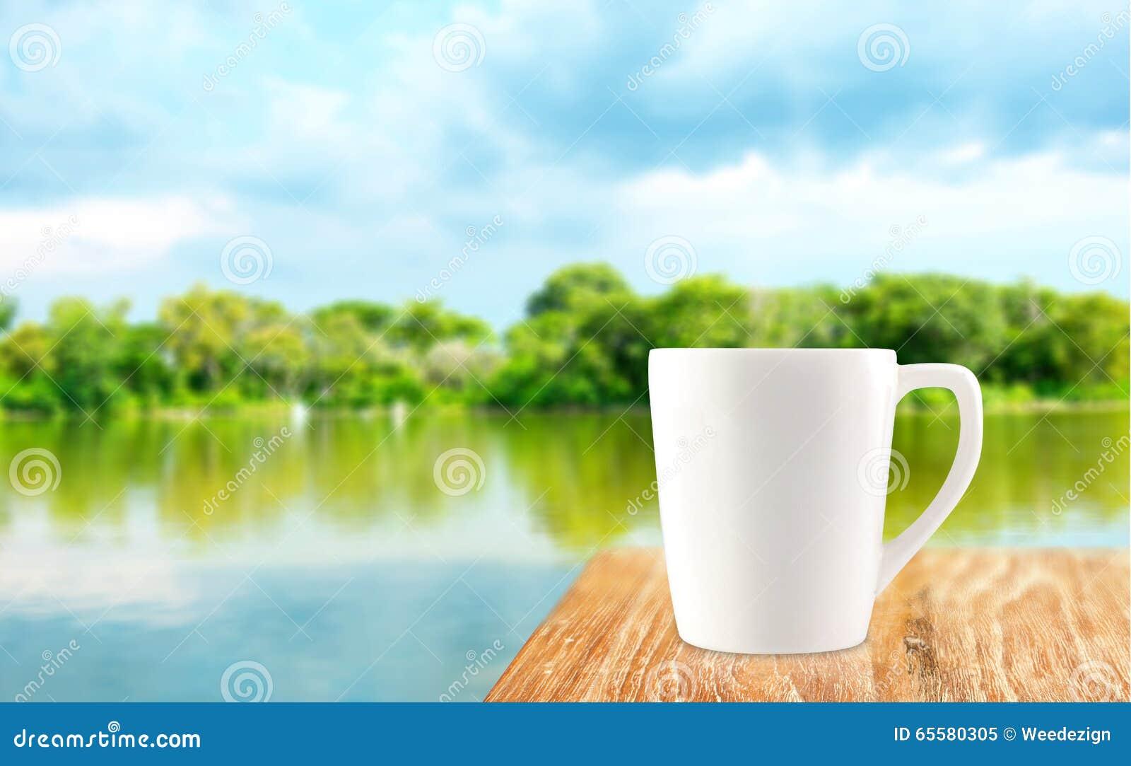 Copo de café branco na tabela de madeira na árvore do borrão e no backgroun da lagoa