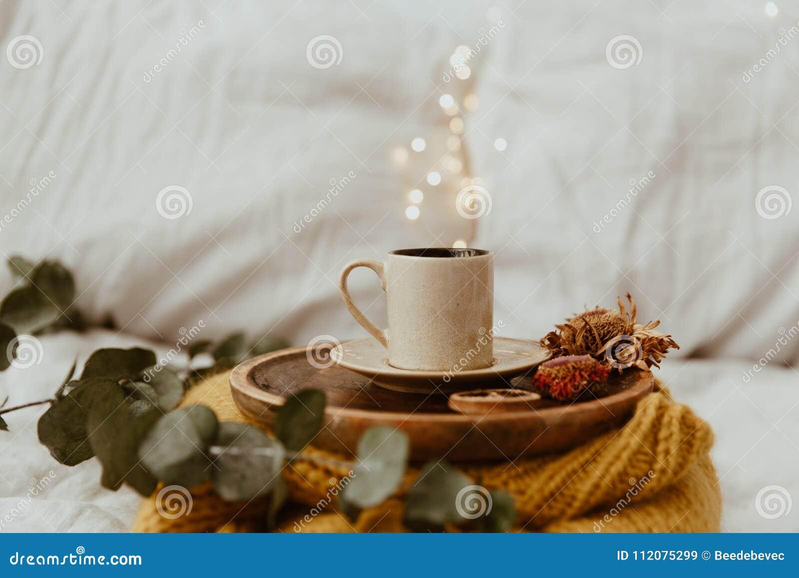 Copo de café colocado em uma bandeja de madeira e em uma camiseta morna com borrão do bokeh do fundo das luzes Manhã na cama