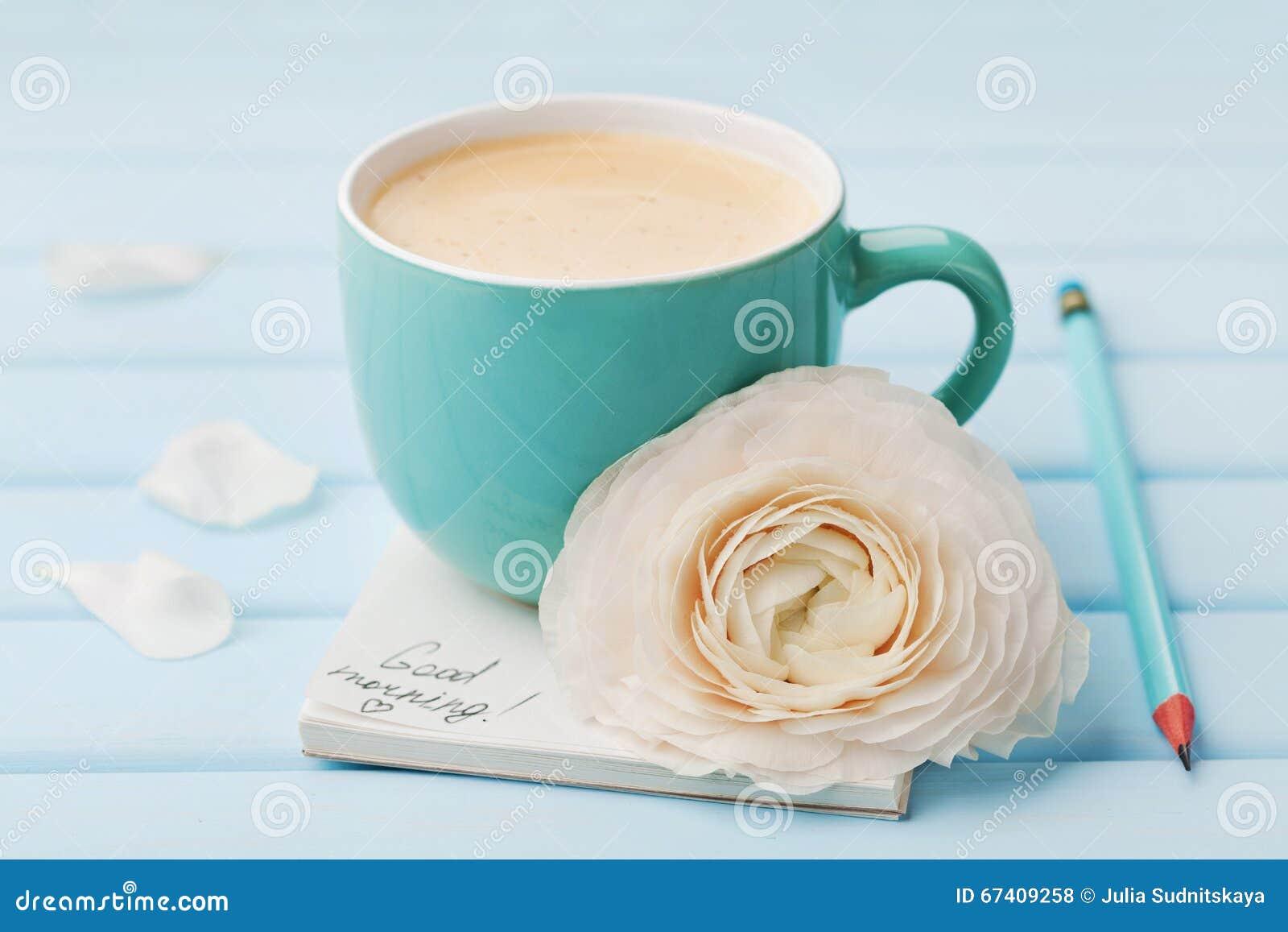 Copo de café com bom dia da flor e das notas da mola no fundo rústico azul, café da manhã